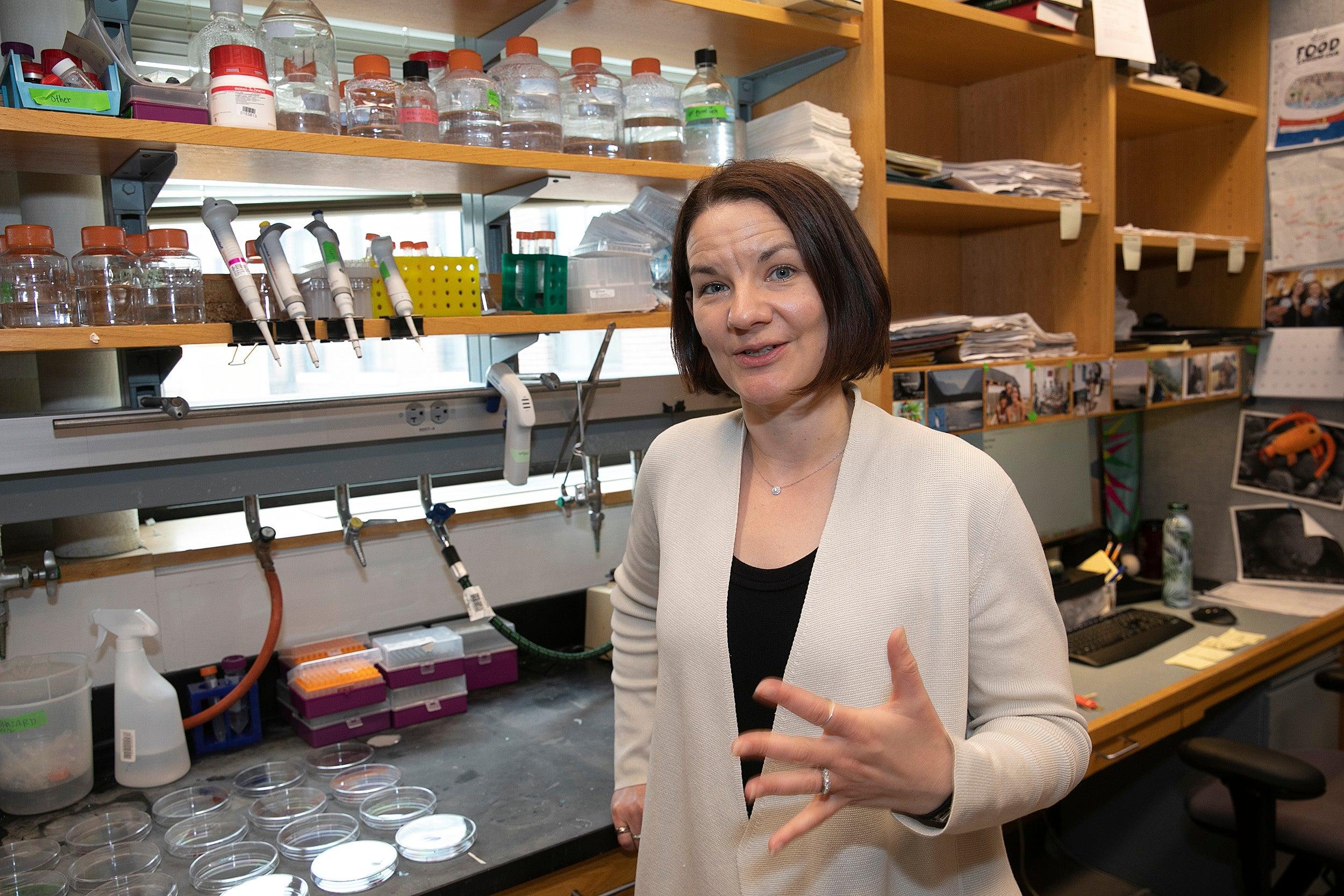 Professor Emily Balskus explains a scientific process in the lab