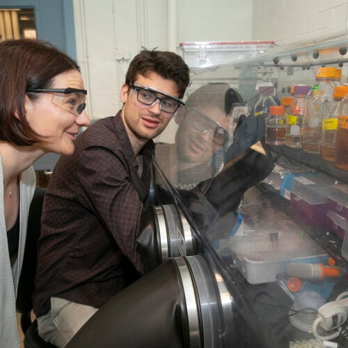 Professor looks over the shoulder of grad student working in the lab