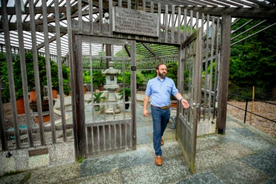 Steve Schneider walking out of bonsai greenhouse at the Arnold Arboretum