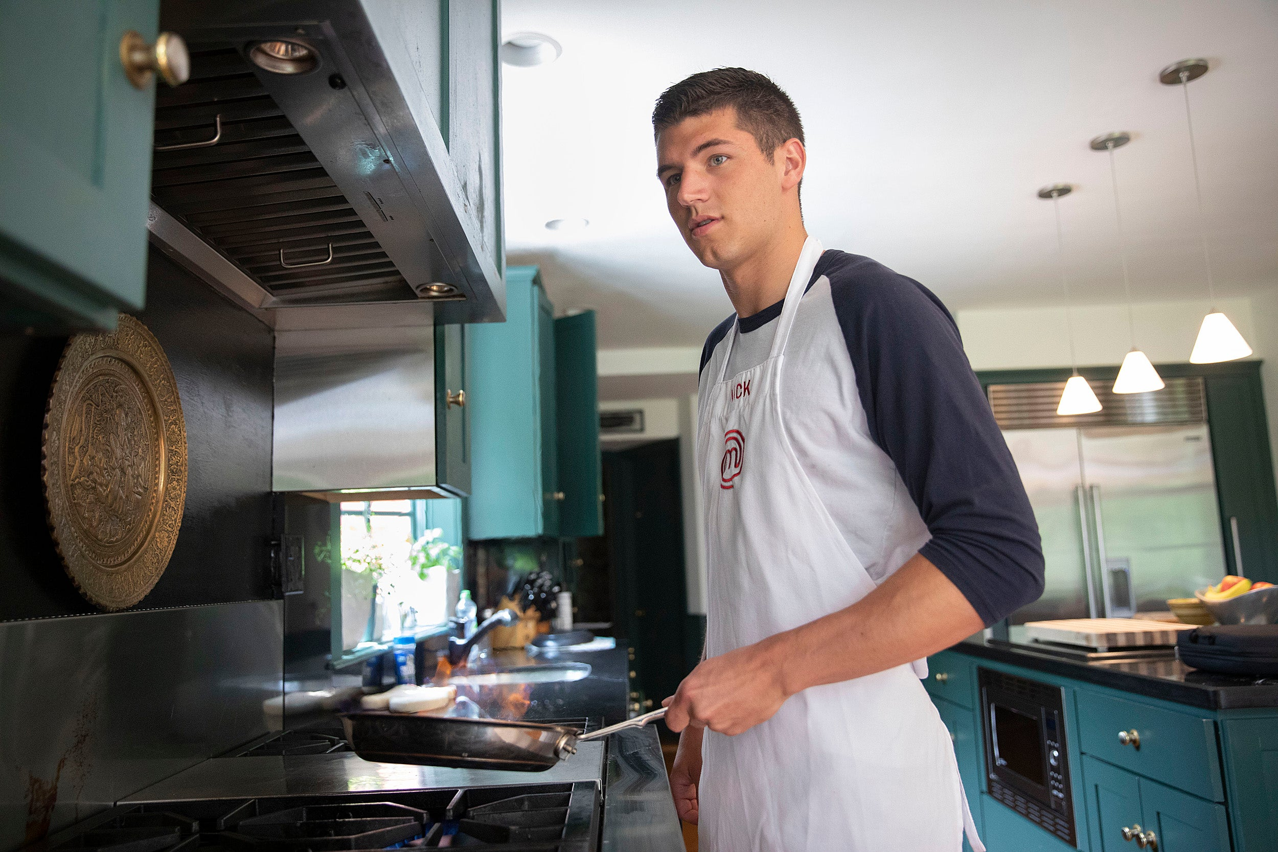 Nick DiGiovanni cooks at his home in Milton.