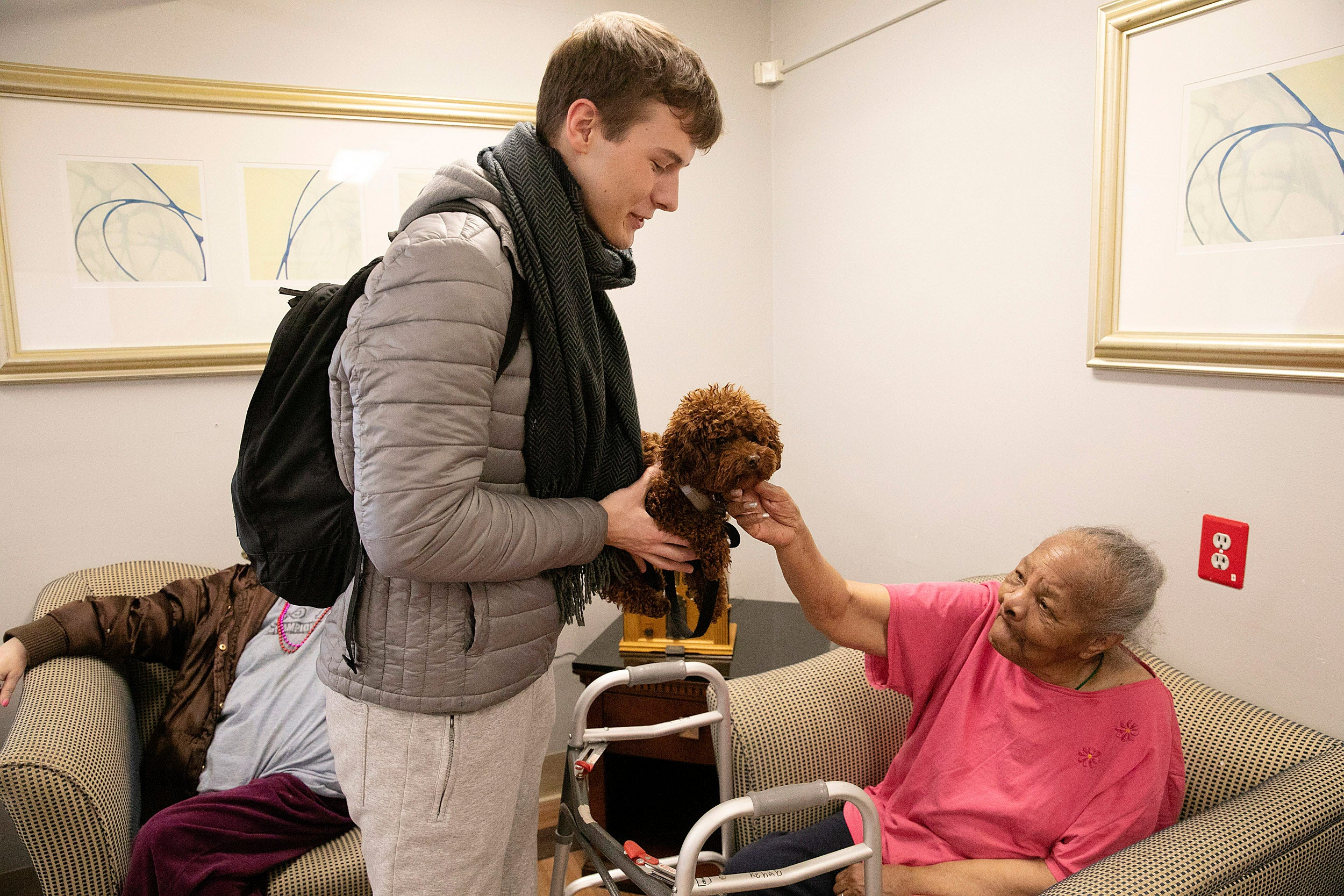 Student holds dog while elderly woman pat dog.