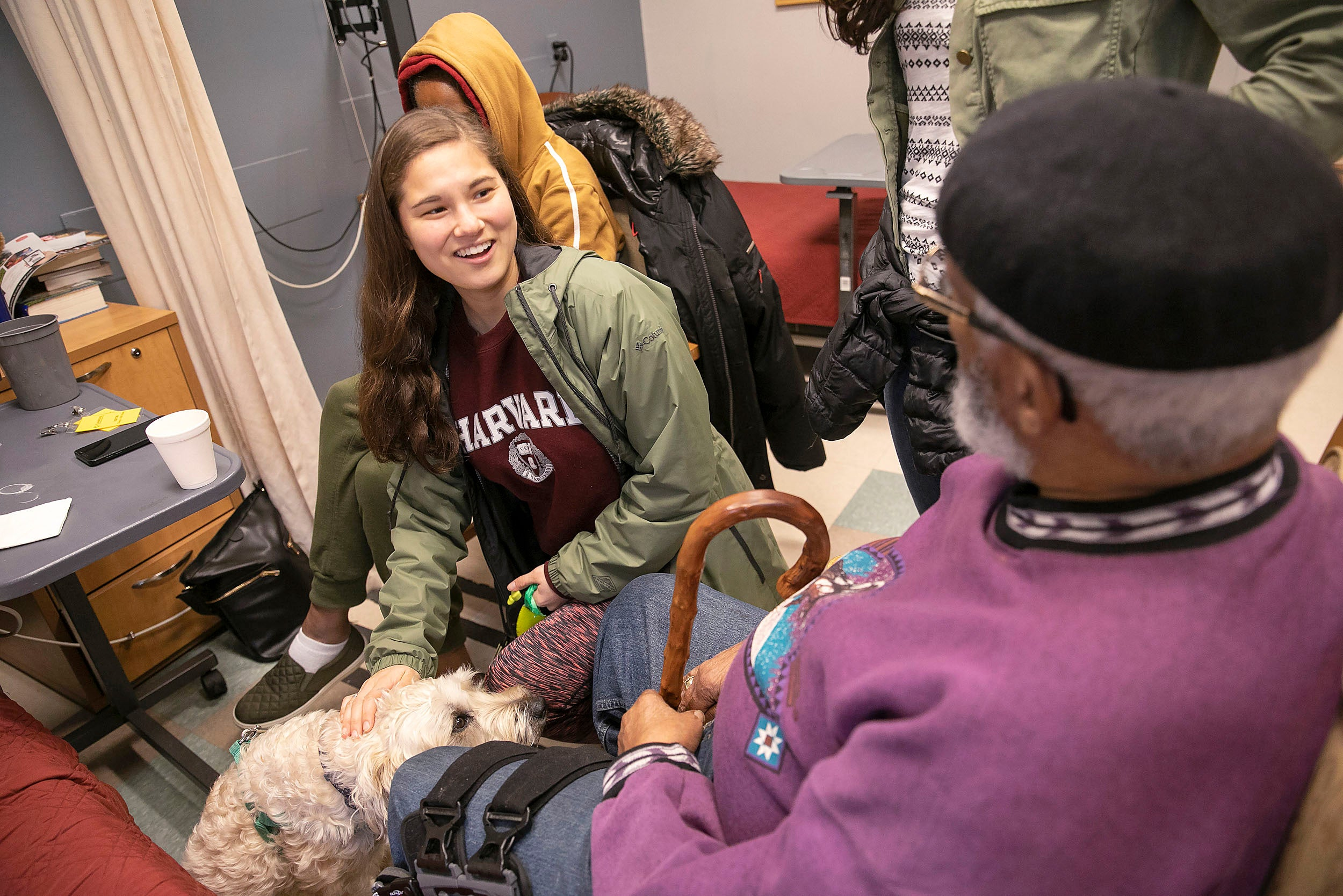 Student and dog visiting residents of rehab center.