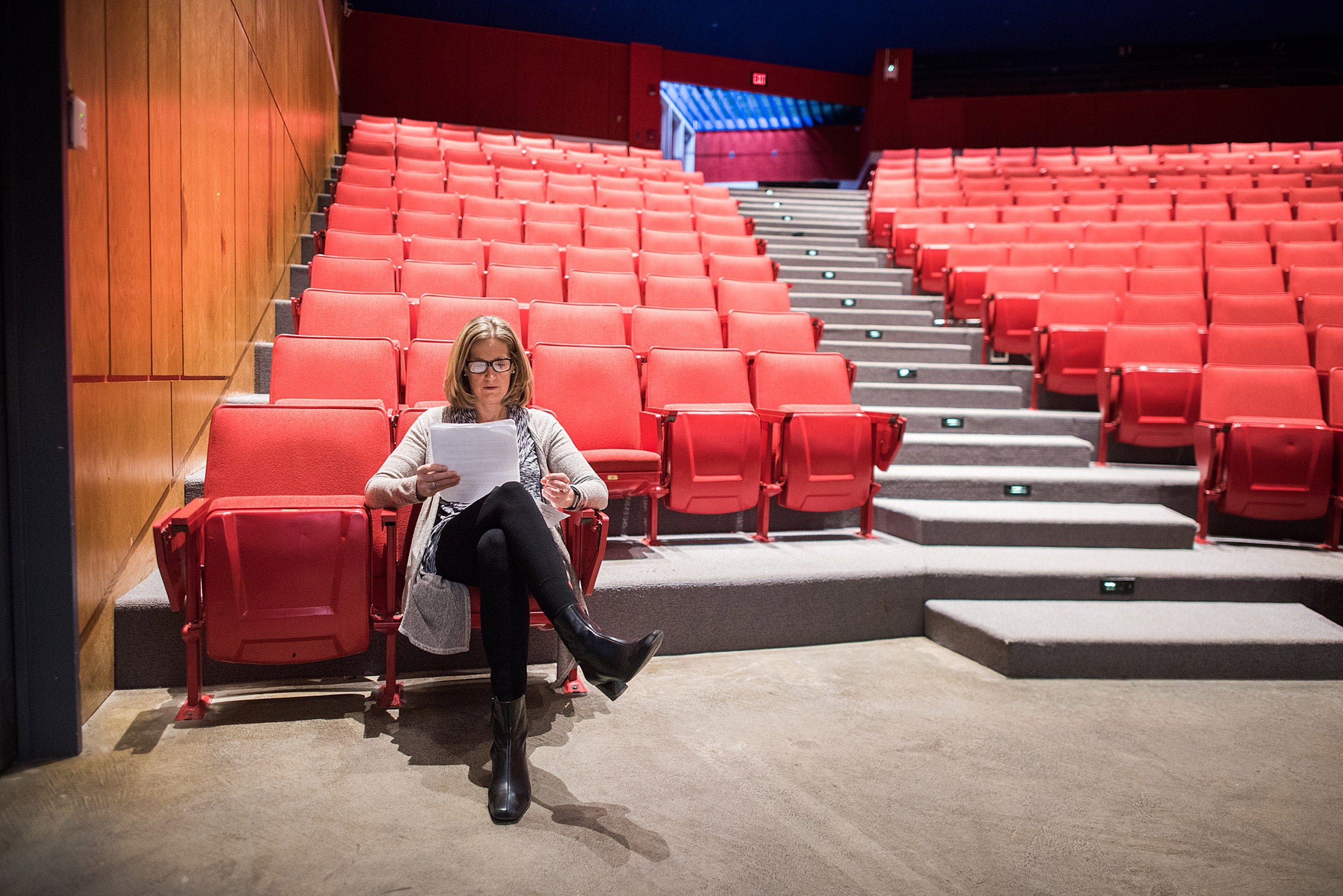 Dean Katie O'Dair sits in an empty theater preparing for a charity comedy night.