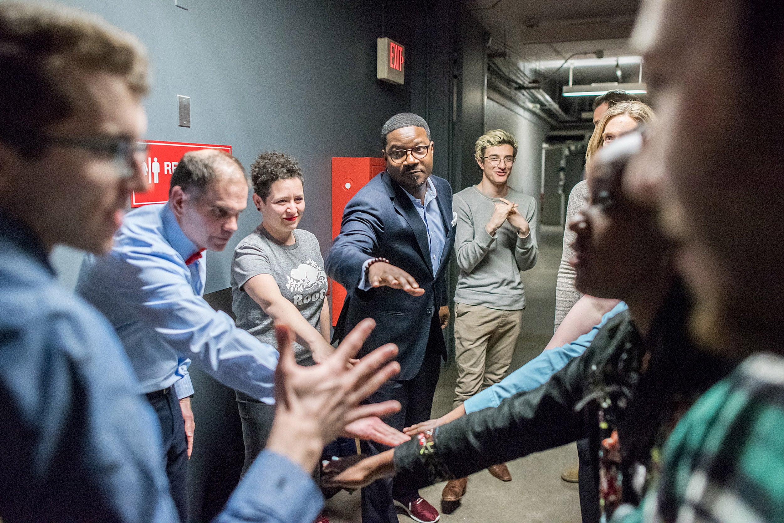Faculty and deans huddle in support backstage.