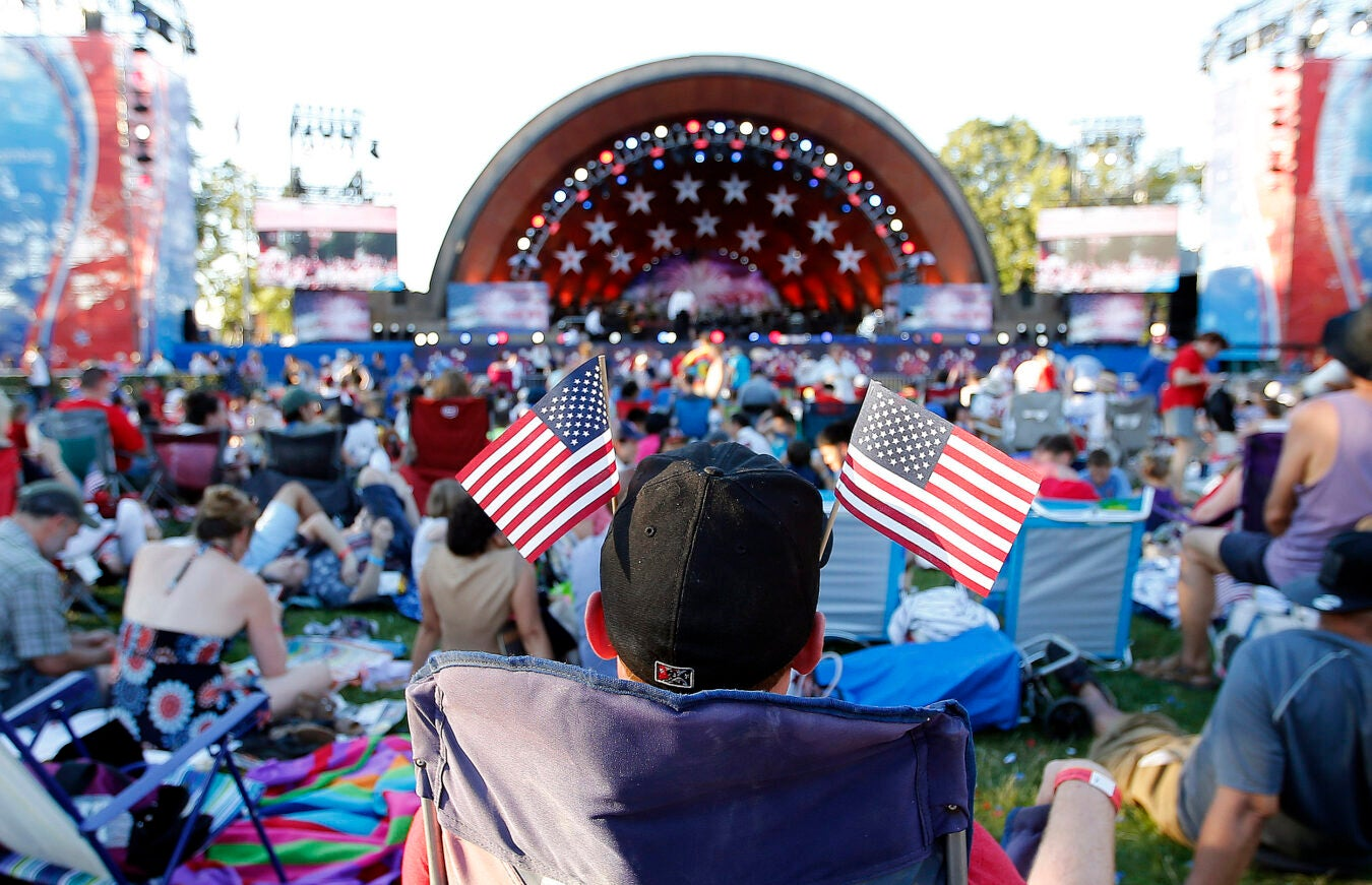 Man with American flags in his baseball cap, facing the Hatch Shell