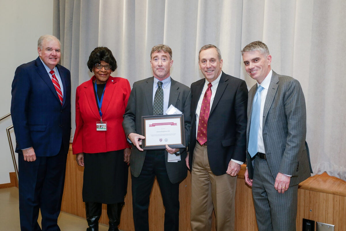 Five people posing for a photo; man in the middle holds an award certificate.