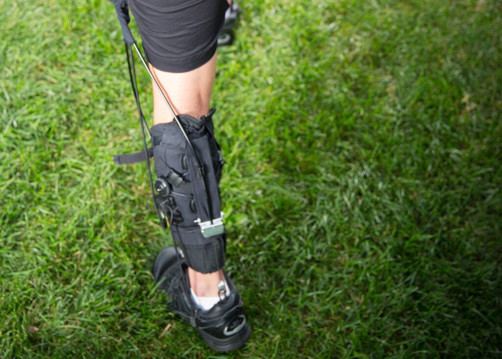 A person wearing a soft exosuit on their leg