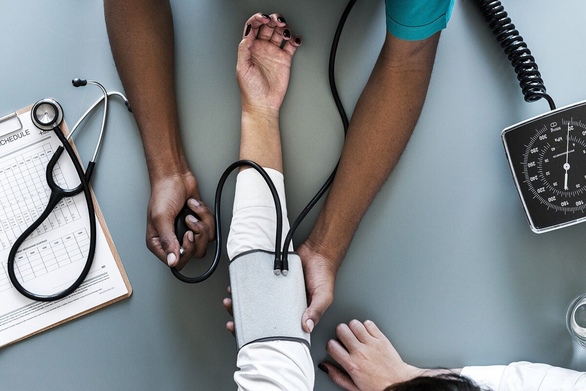 overhead view of a doctor taking a person's blood pressure