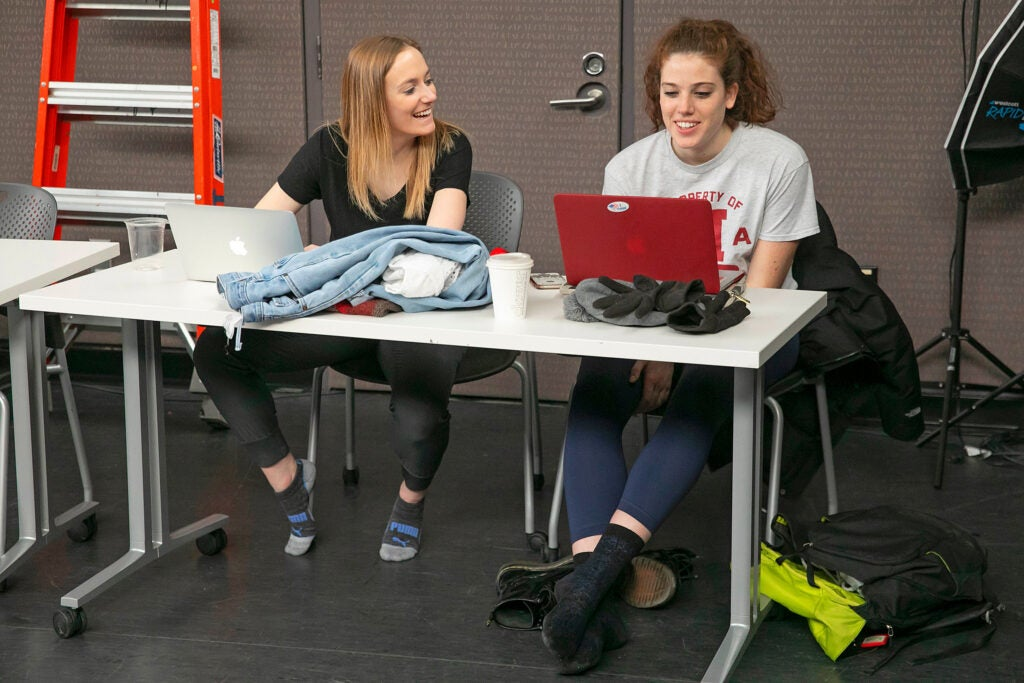 Mara Milner and Anna Antongiorgi sit at a table with laptops during a break.