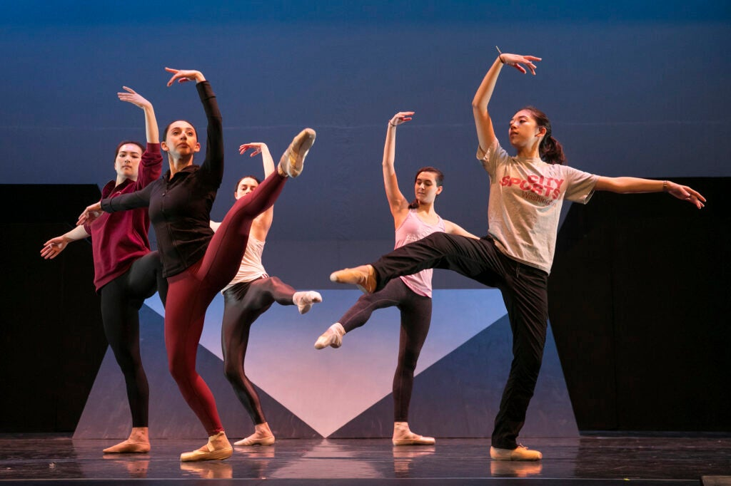 Five dancers pose with arms and legs outstretched.