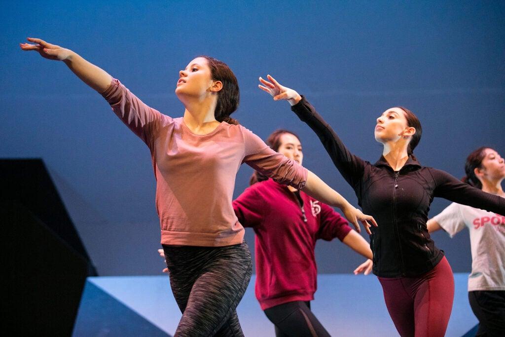 Dancers form a line raising arms.