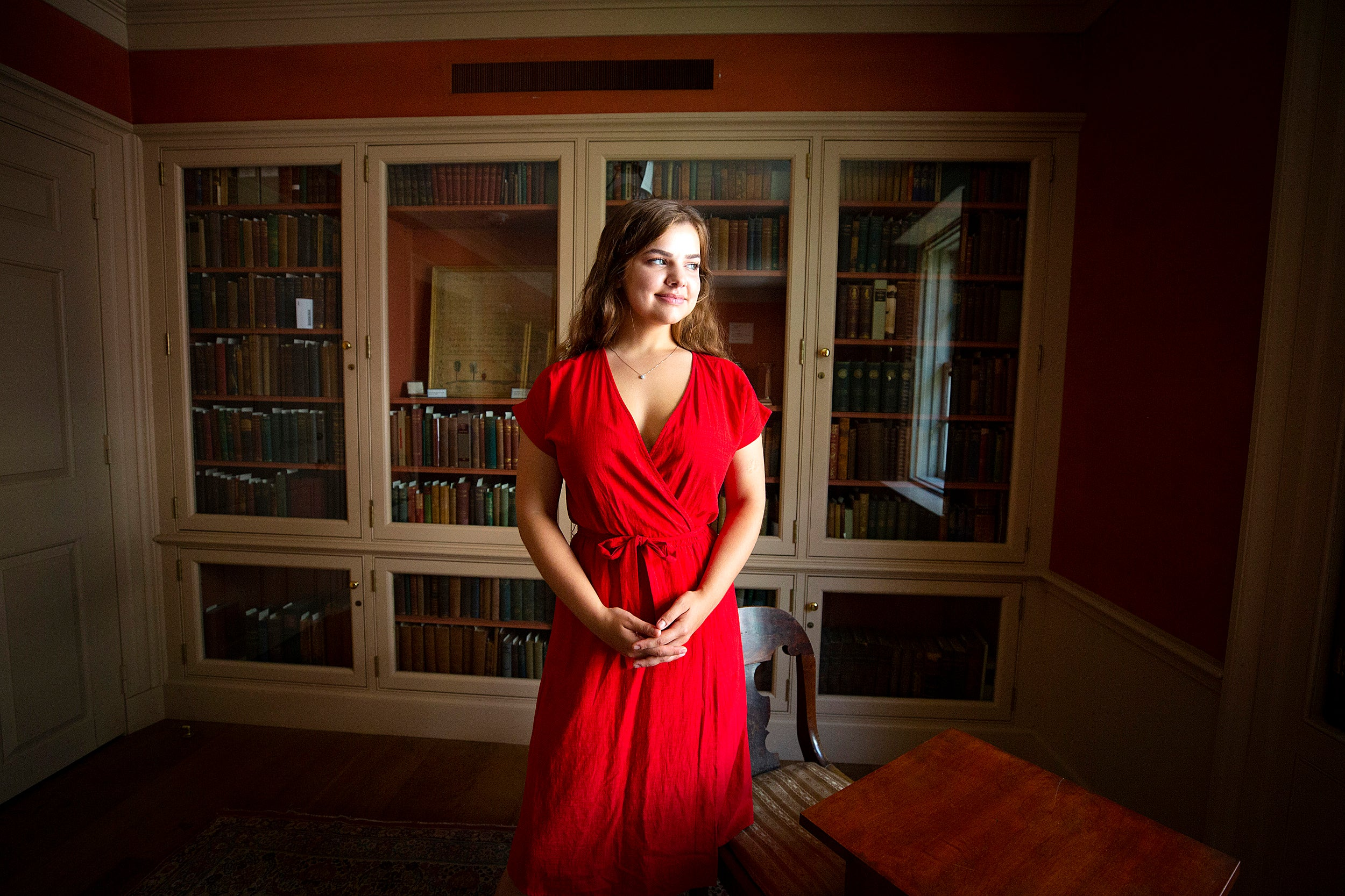 student in a red dress in the library