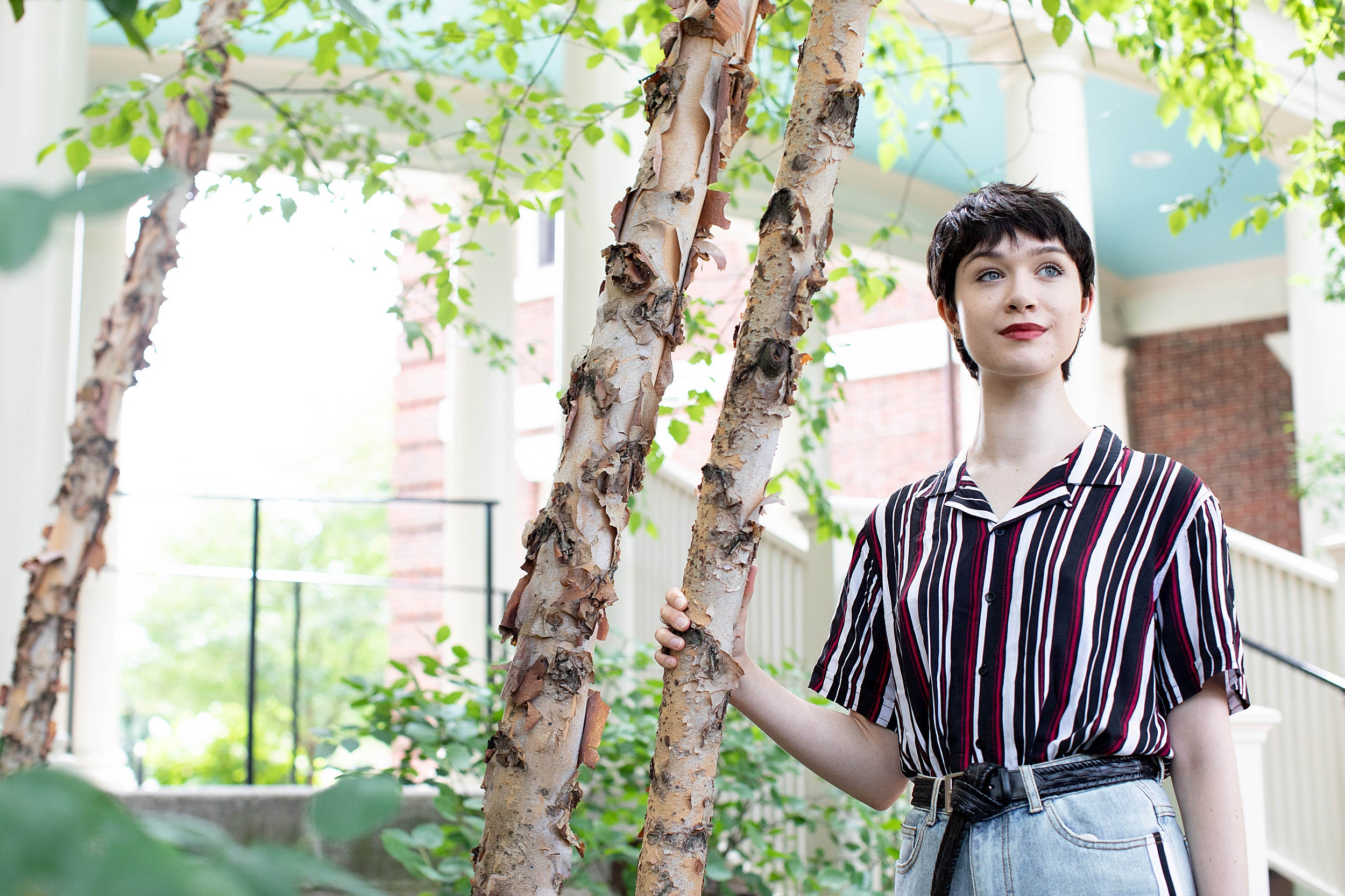 student in a striped shirt next to a tree