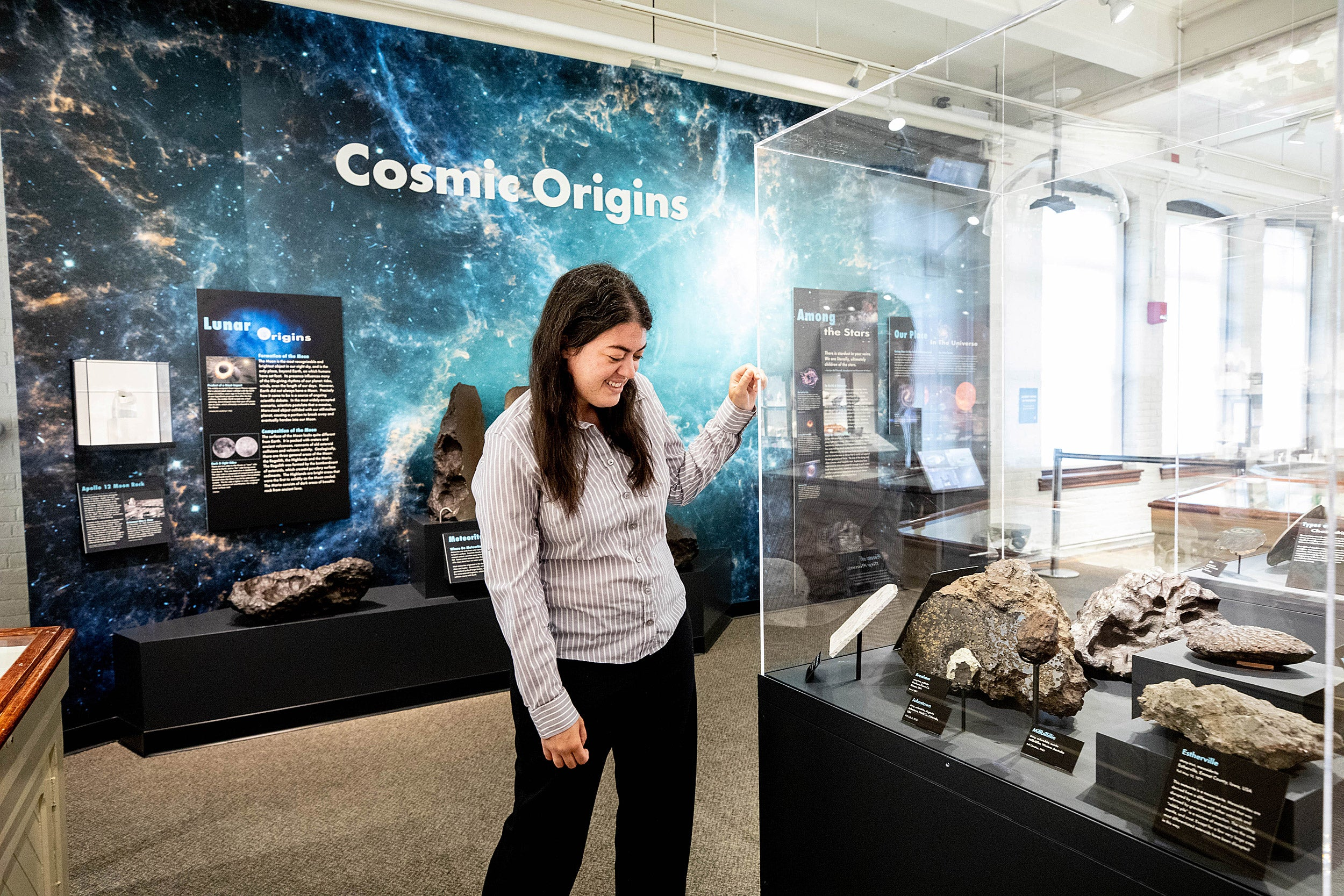 Woman looking at space rocks in a display case