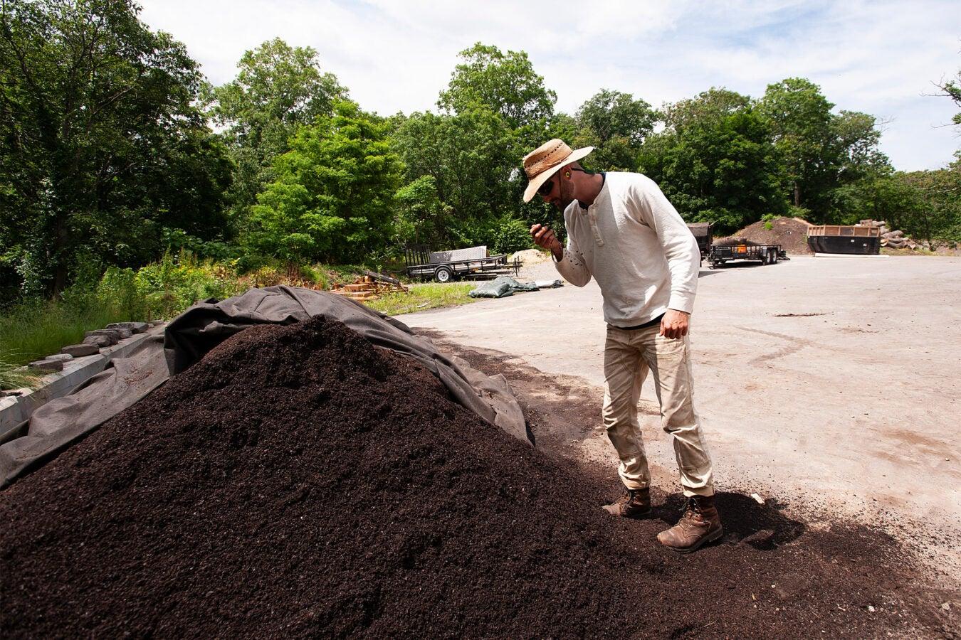 Man examines compost pile