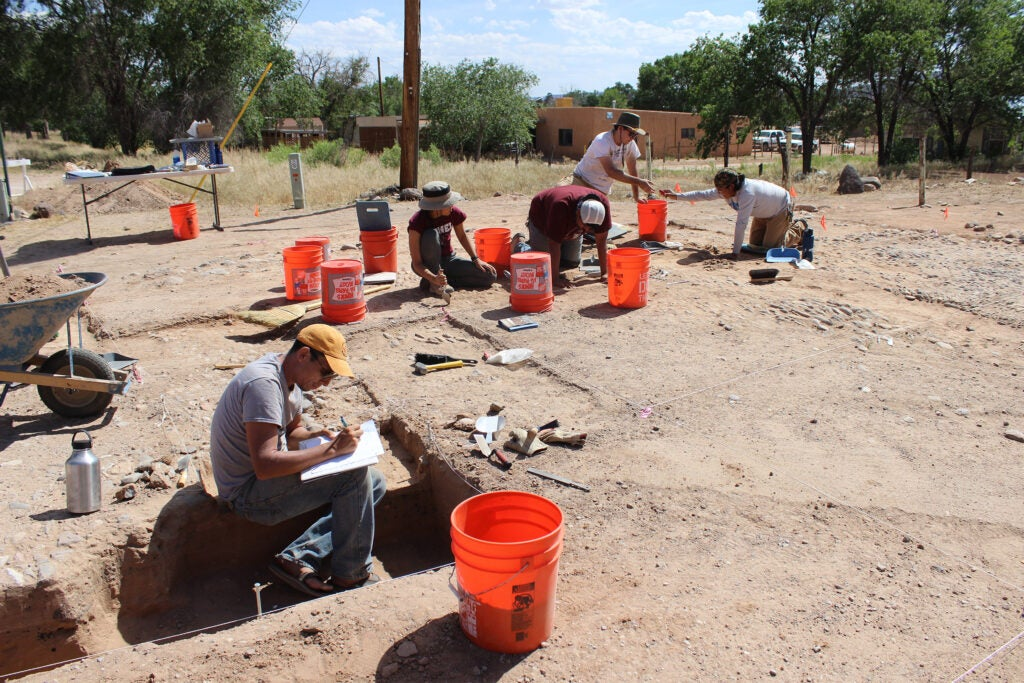 Harvard students and tribal members working at archaelogical dig
