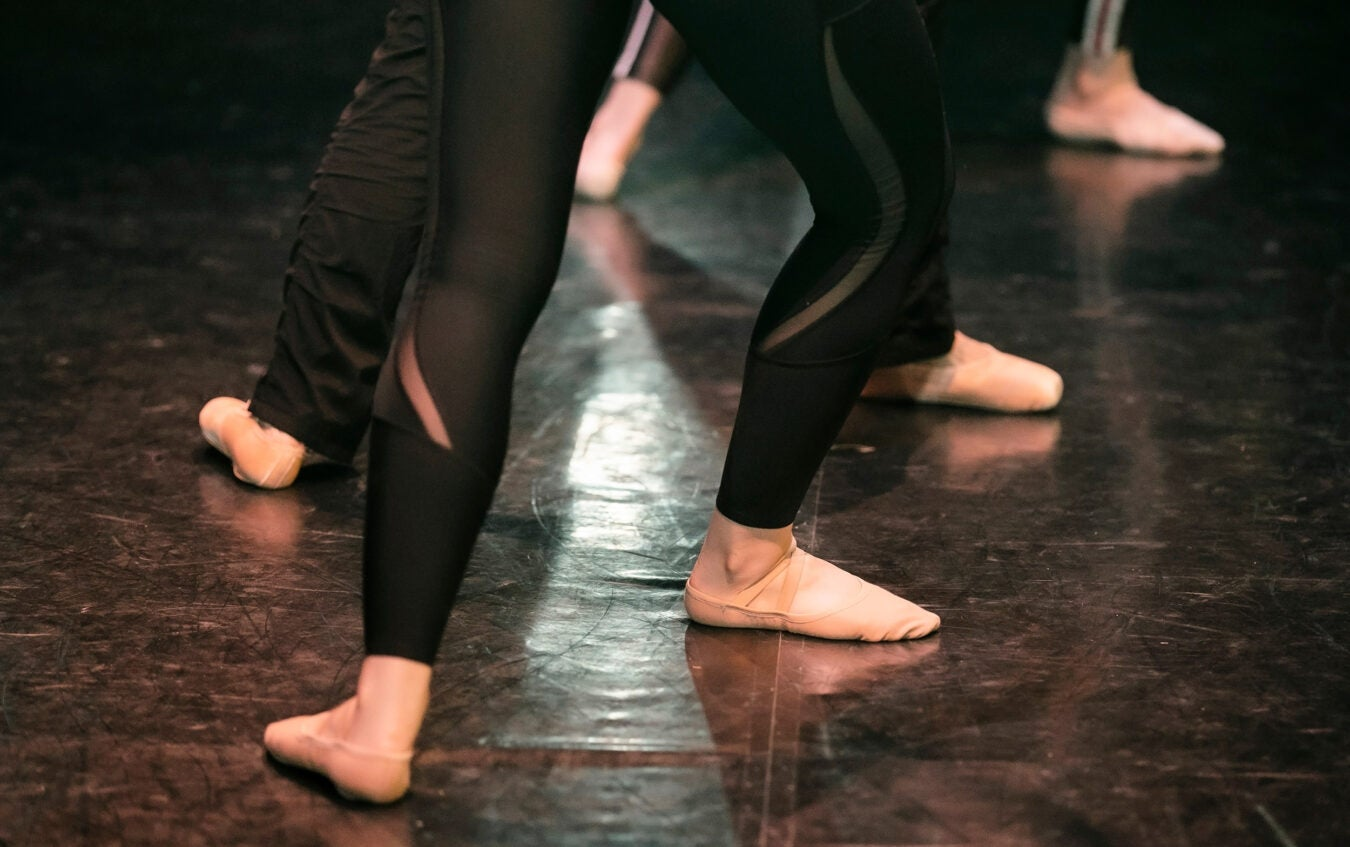 Detail of ballet dancers placing feet in fourth position.