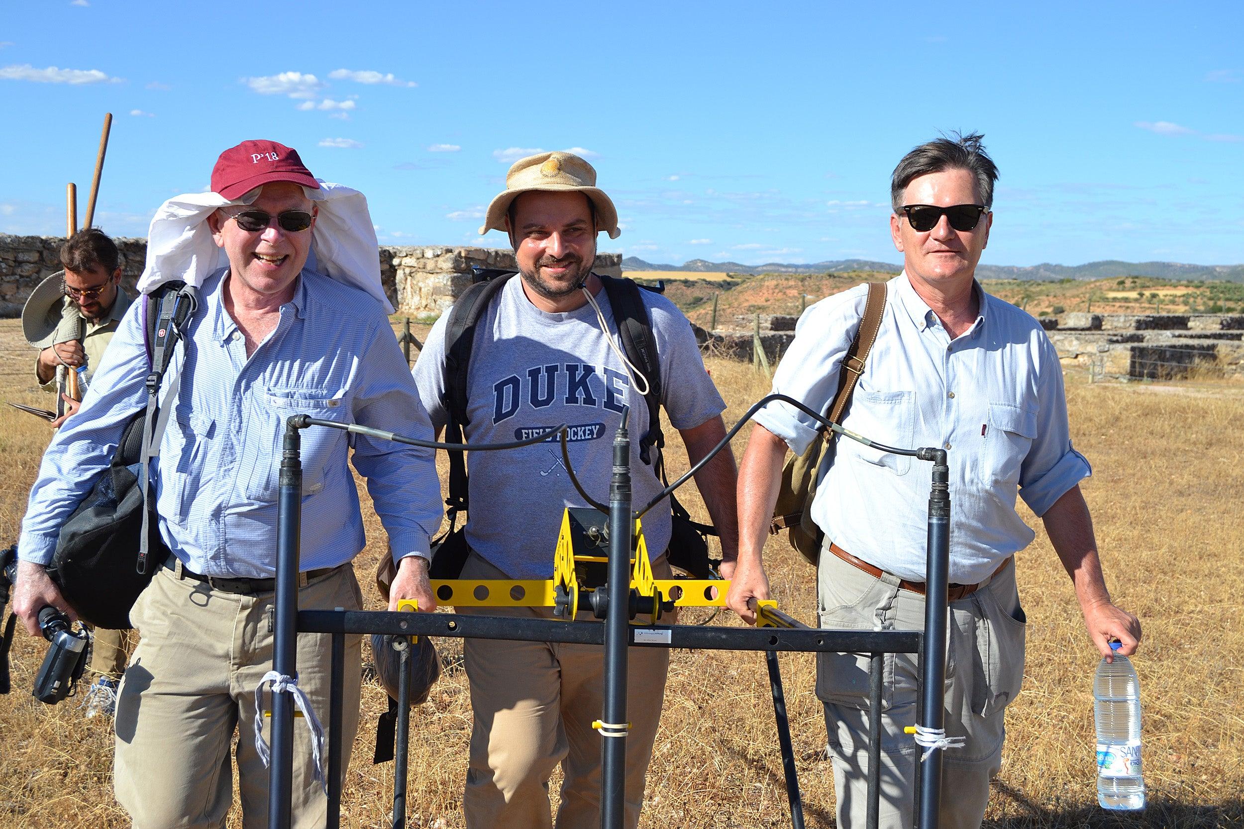 Three men holding excavating tool