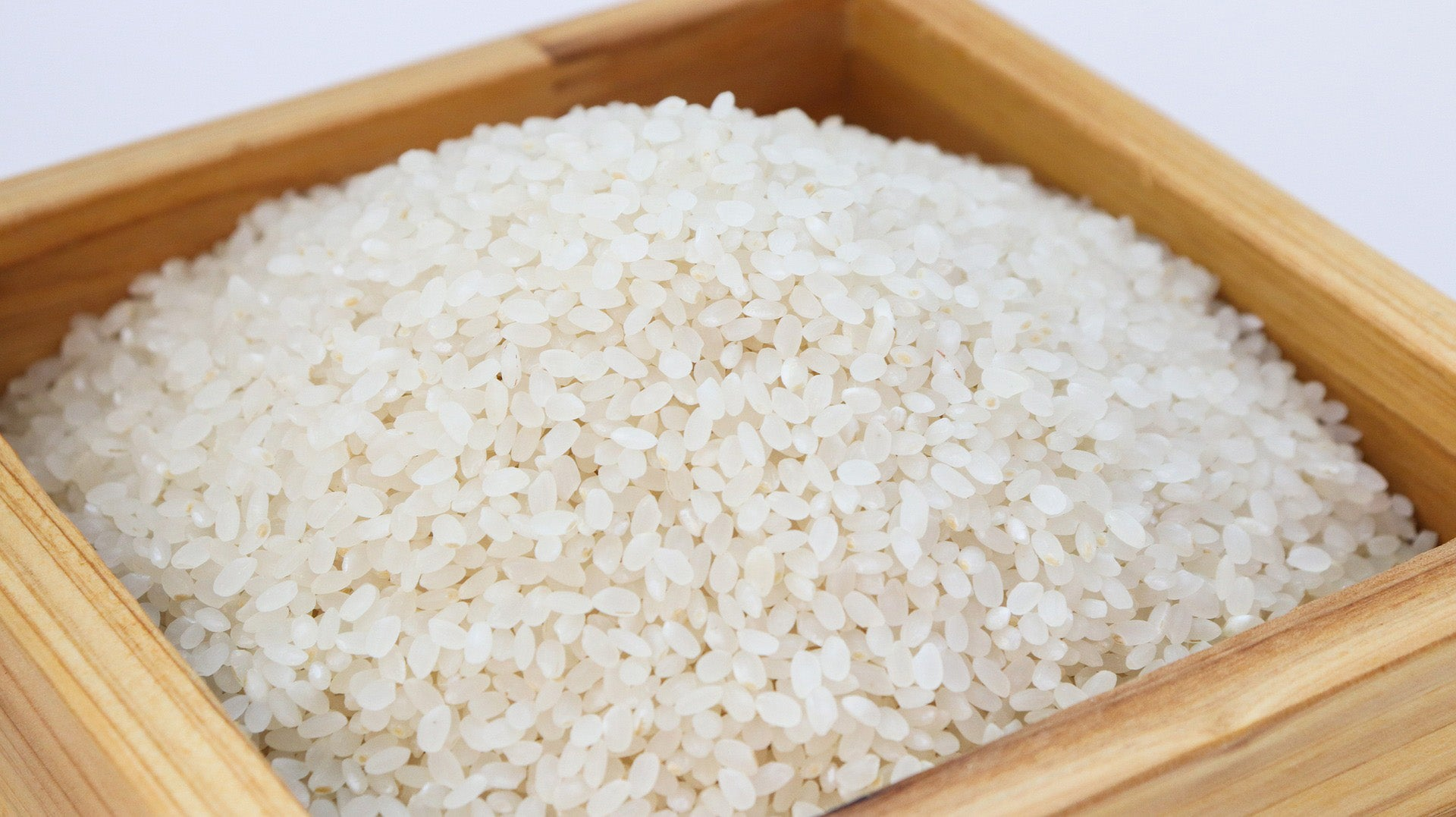 Uncooked rice in a wooden container