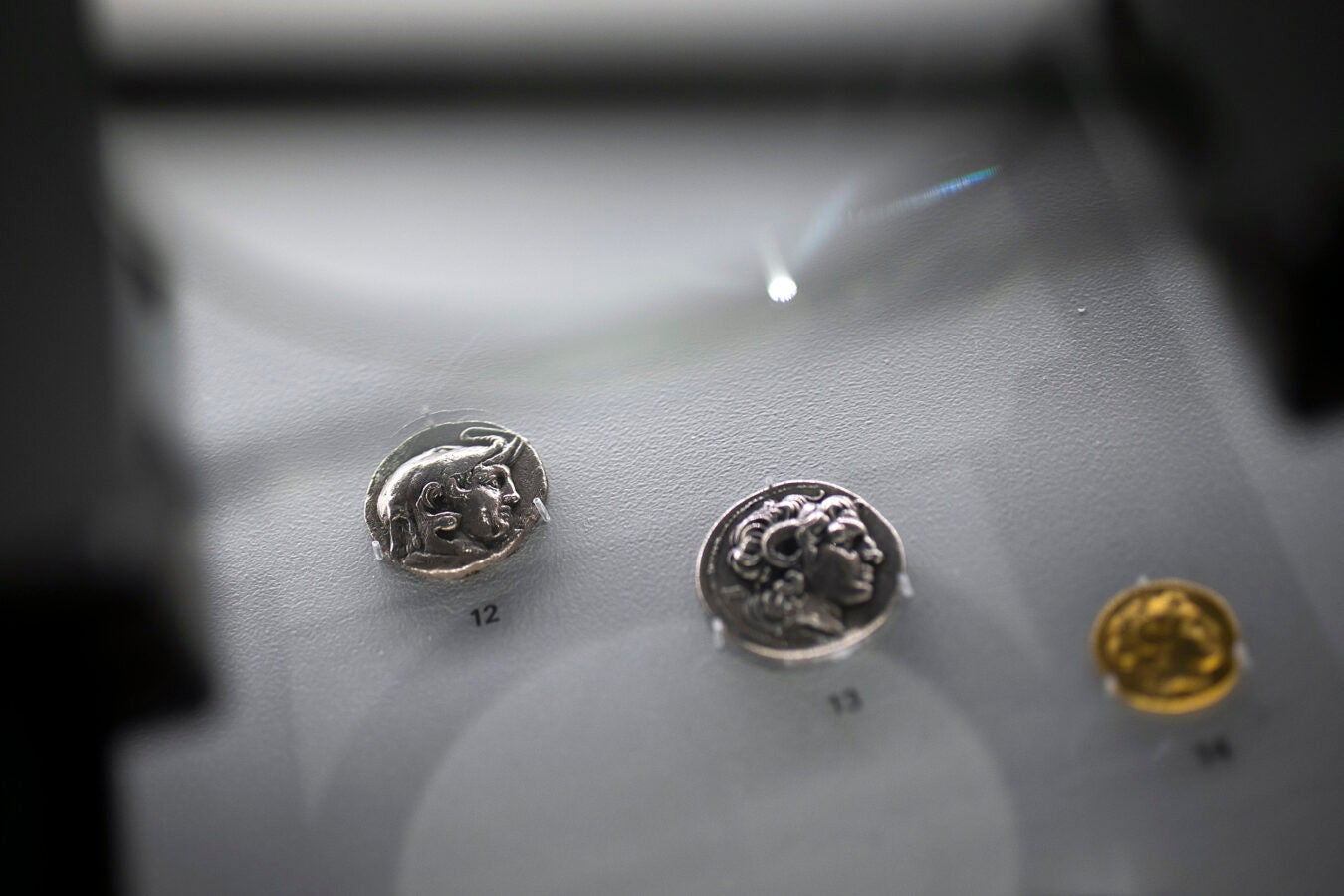 three ancient coins in a display case