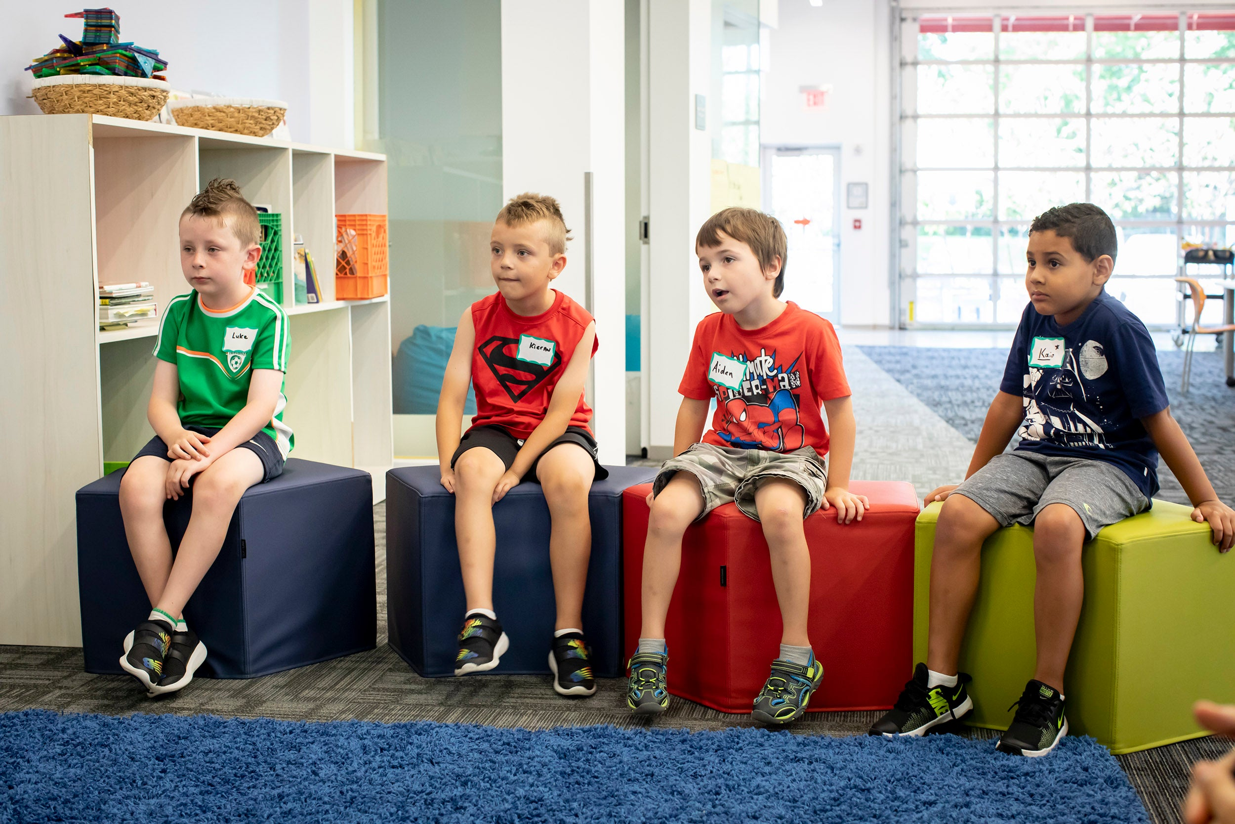 Luke Scanlon (from left), Kieran Bligh, Aiden Kiley, and Kaio Marques listen during poetry class.
