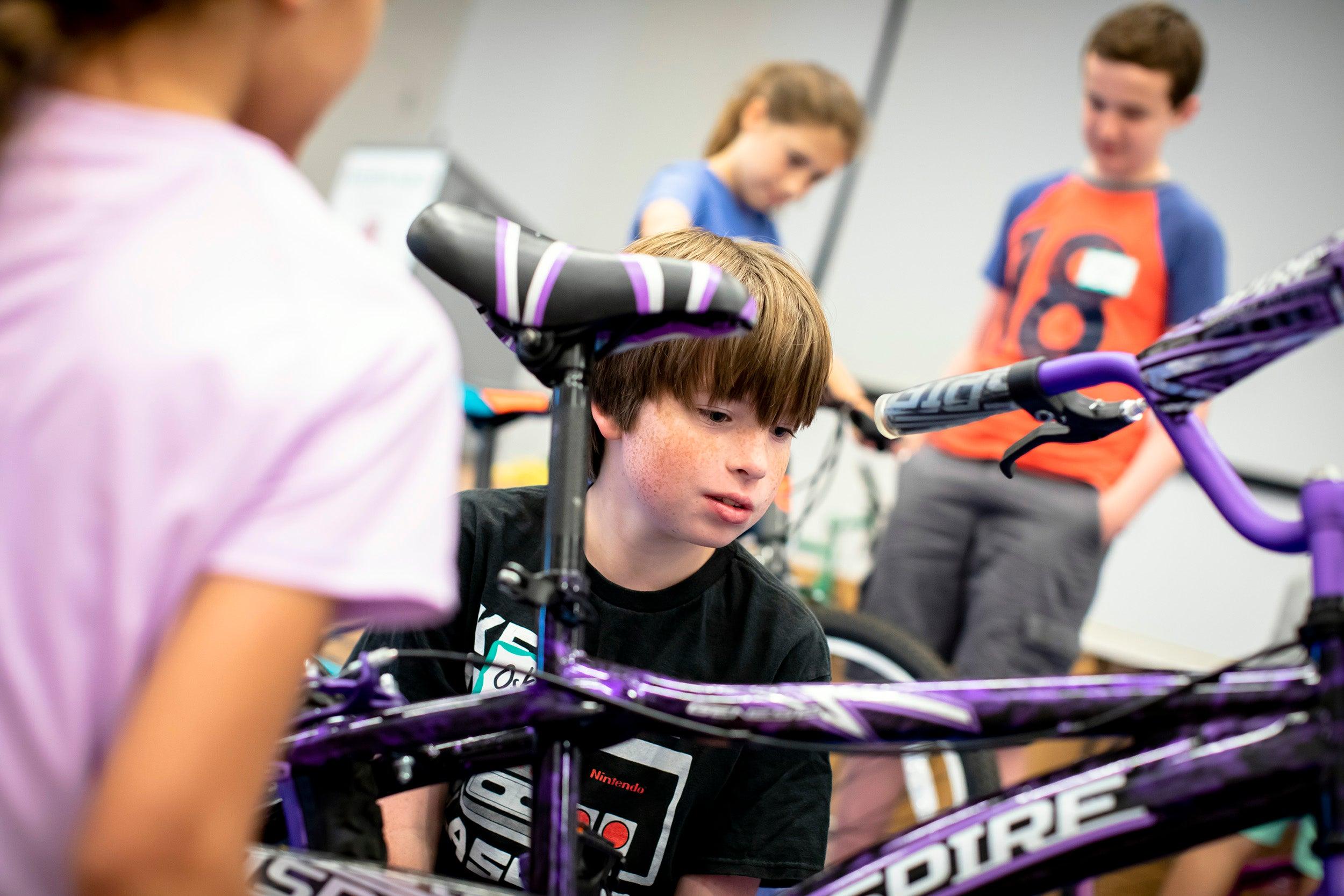 Oskar Monahan repairs a bicycle.