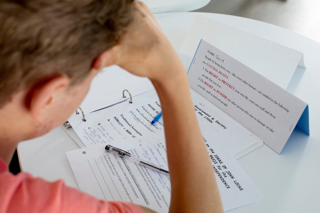 A student reads class papers.