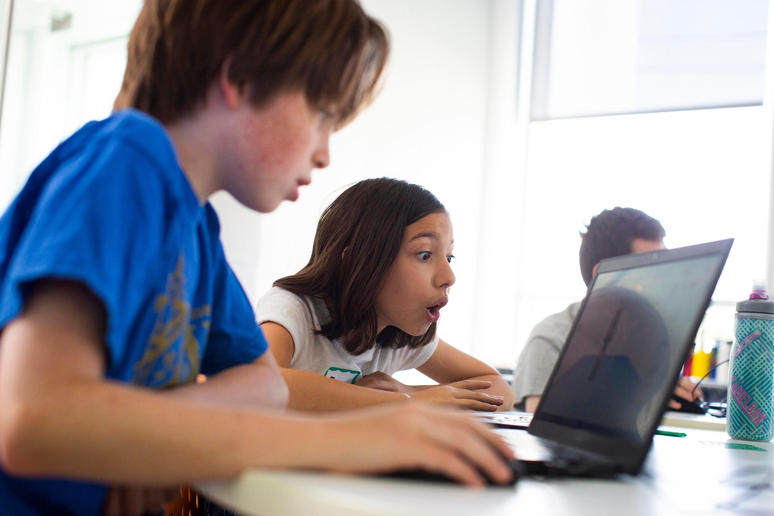 Oskar Monahan and Eva Lynch look at a computer.