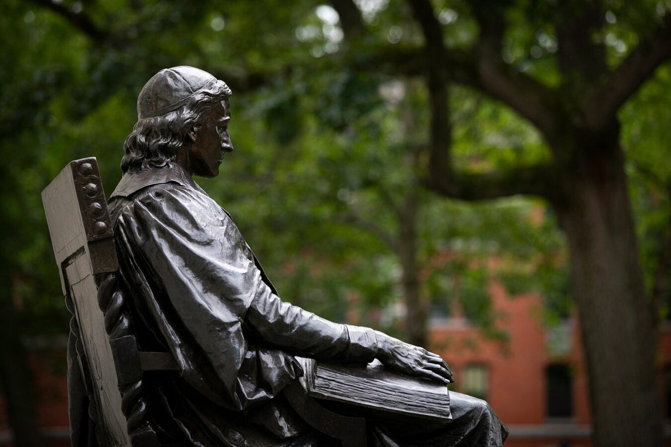 John Harvard statue with the Yard in the background.