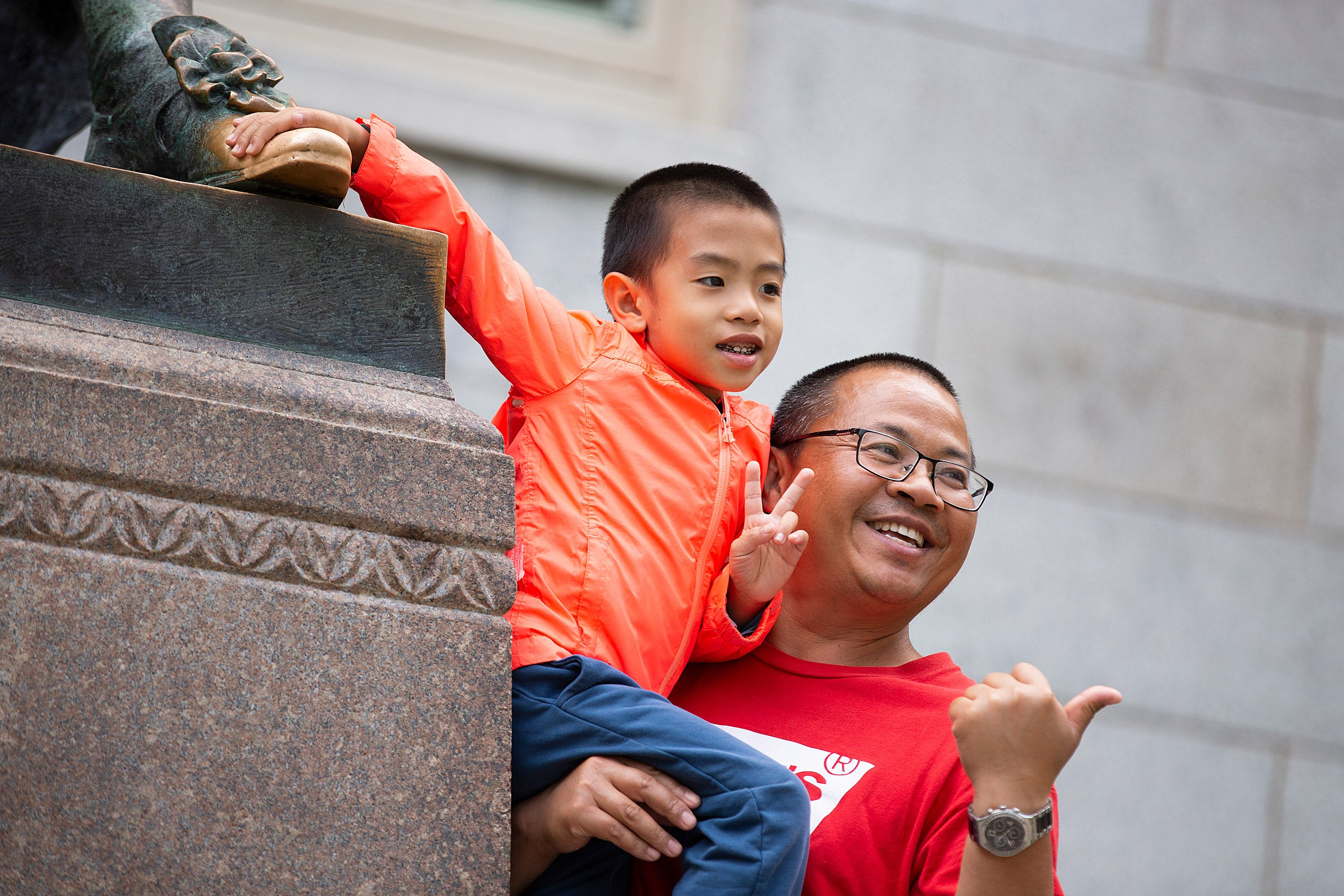 Father holds 6-year-old son who touches the statue's foot.