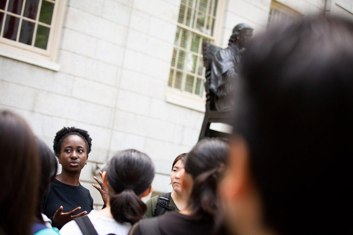 Sammota Mwakalobo leads a tour group by the statue.