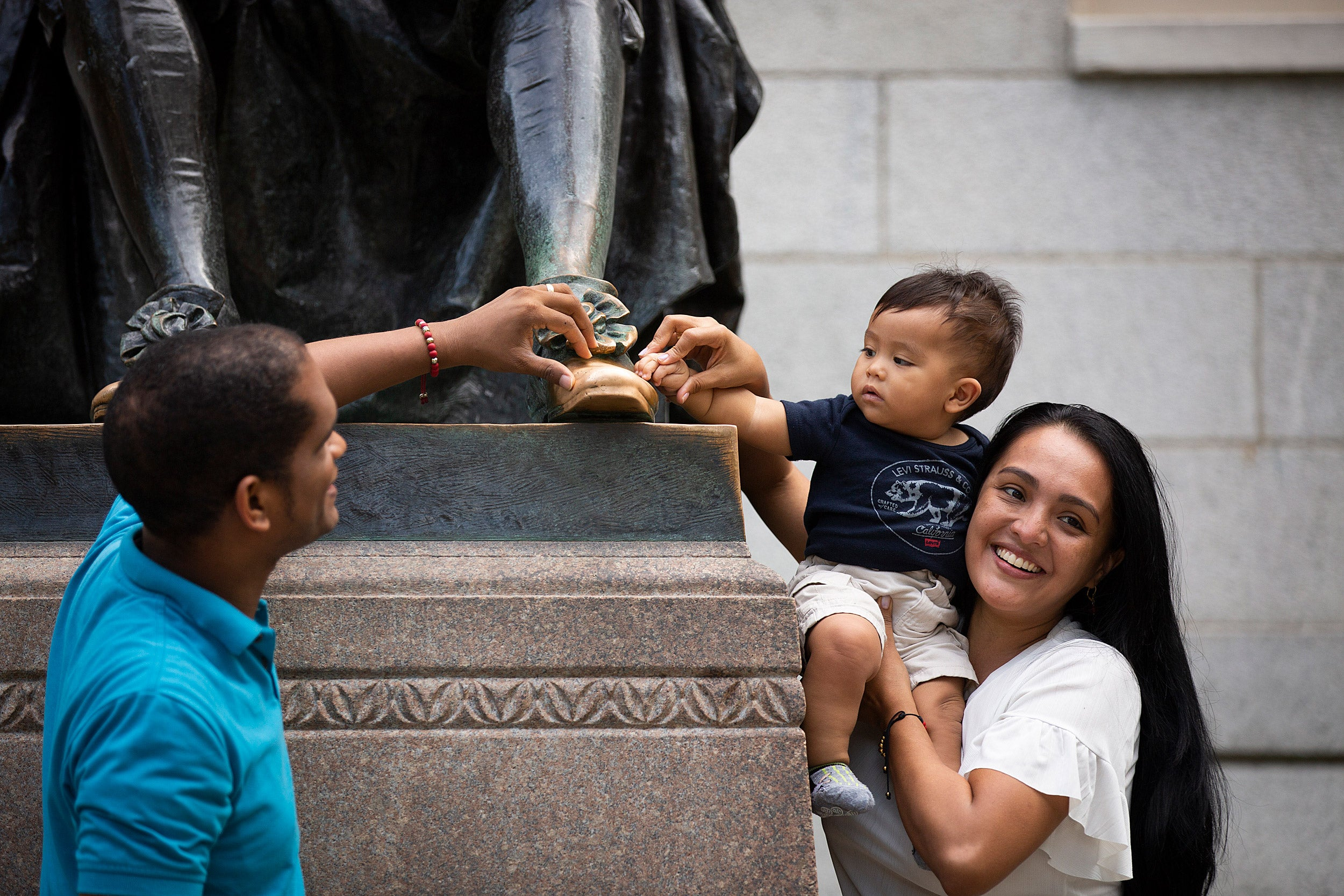 A couple with 9-month-old child pose at the foot of the sculpture.