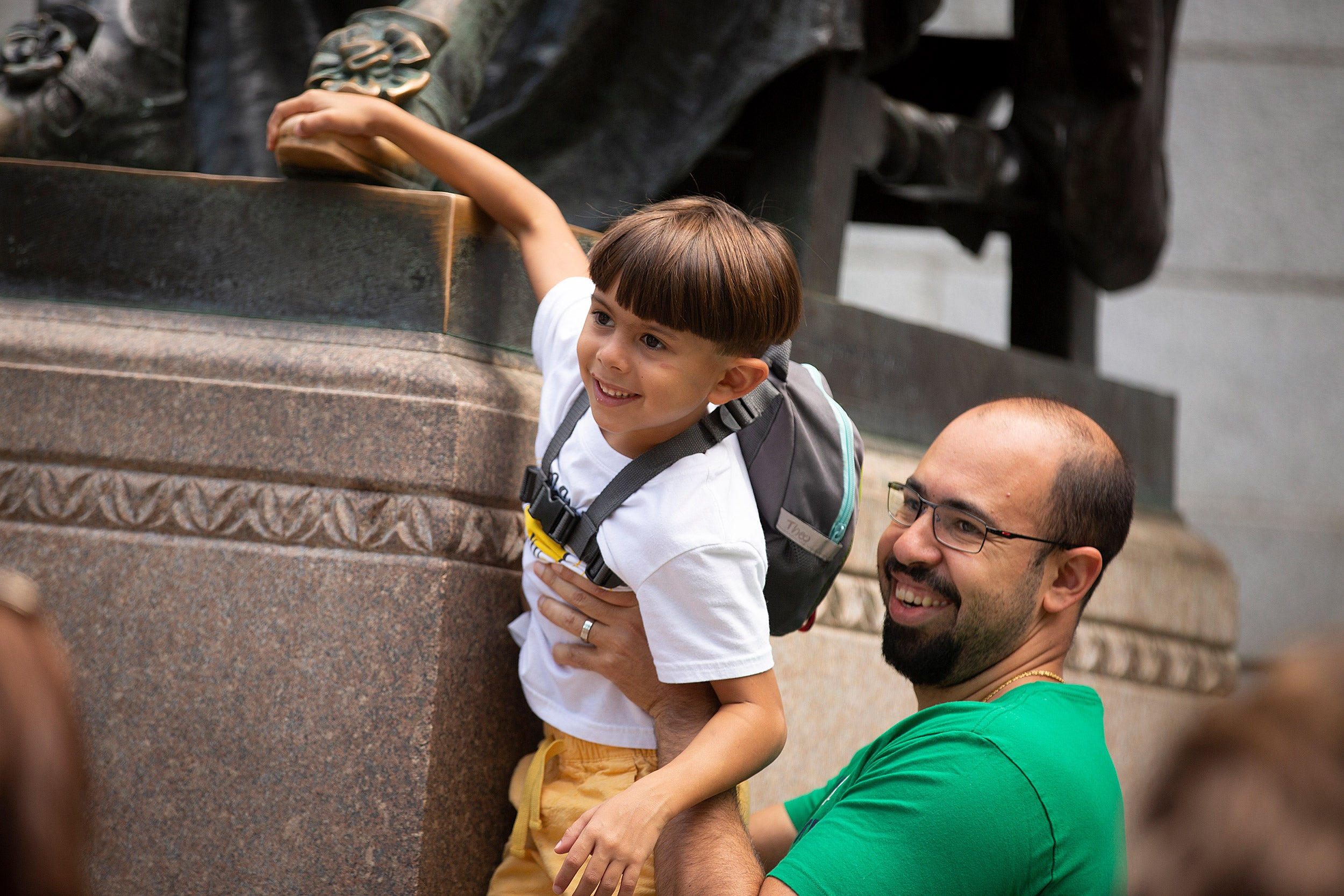 A father hoists his 7-year-old son to reach the foot of the statue.