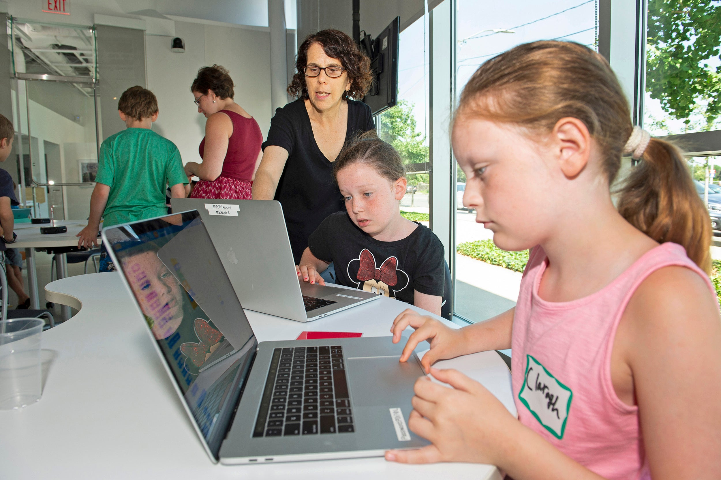 Instructor Sharon Jason teaches students on computers.