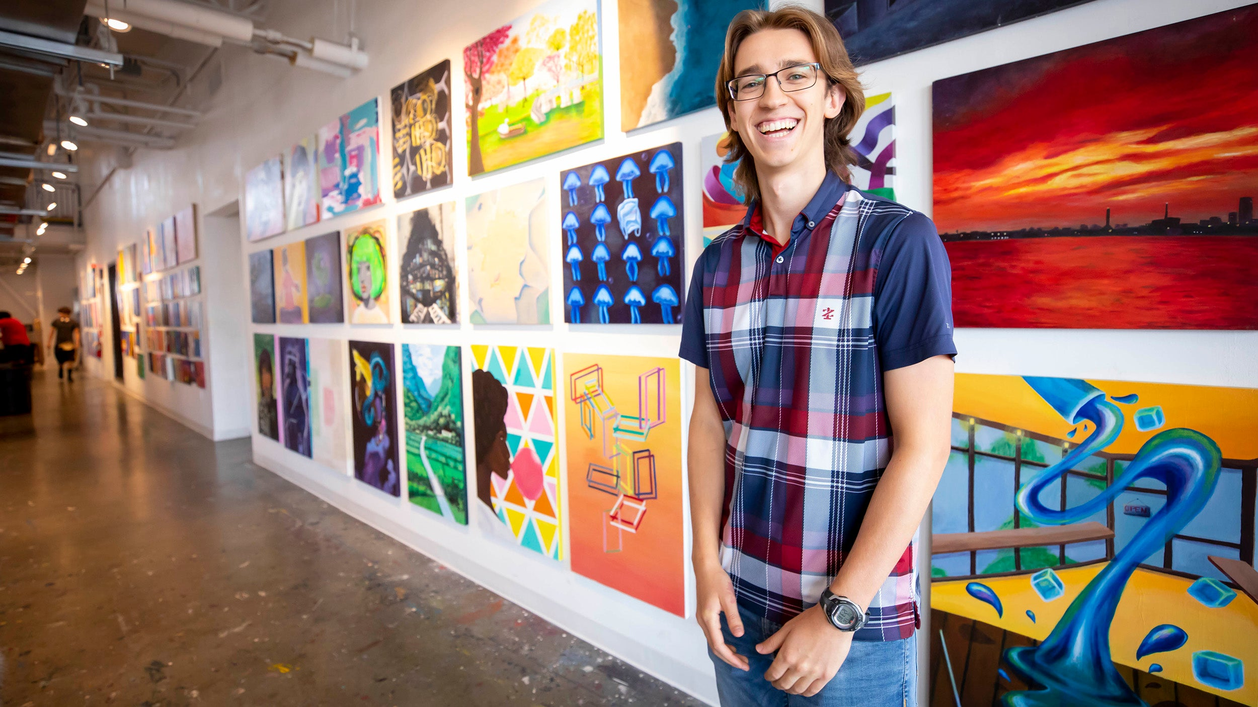 Harvard first year student standing in front of student artwork on wall.