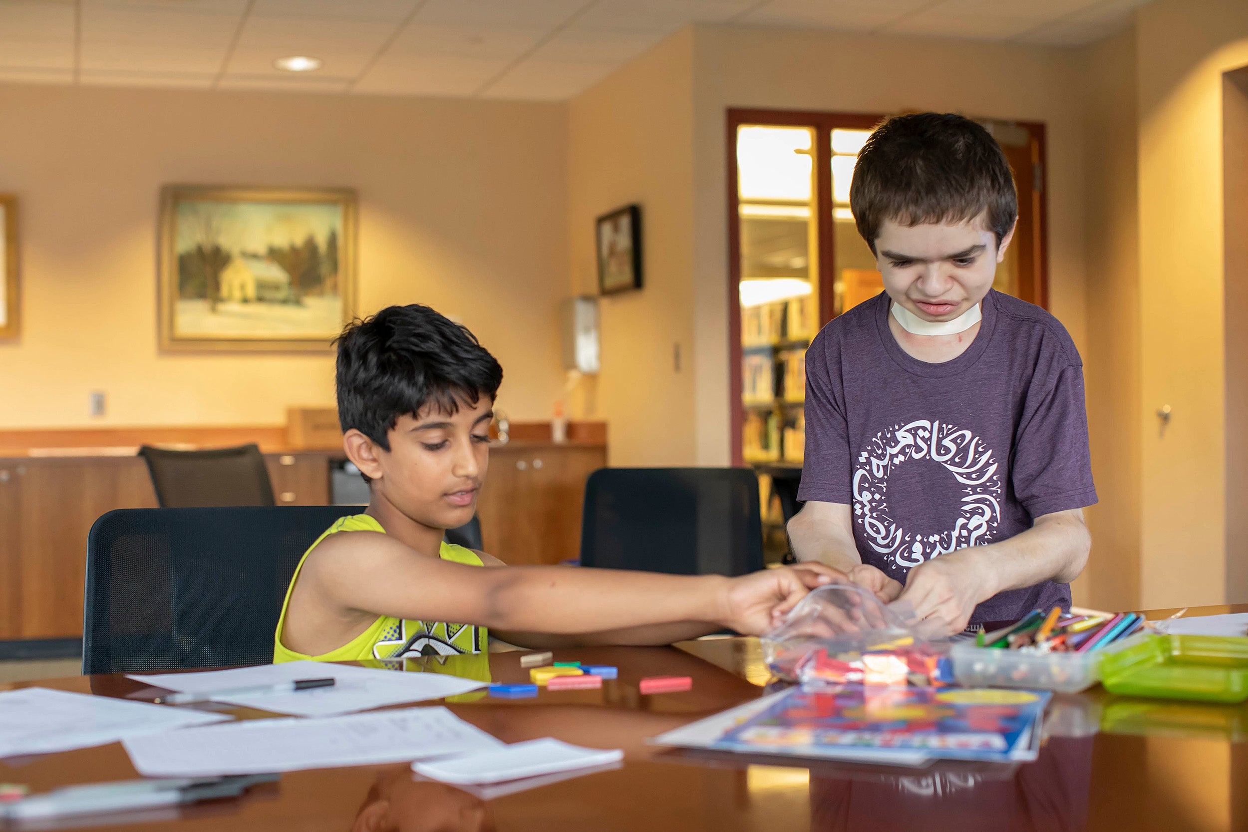 Ben Elwy works with an elementary school student at the library