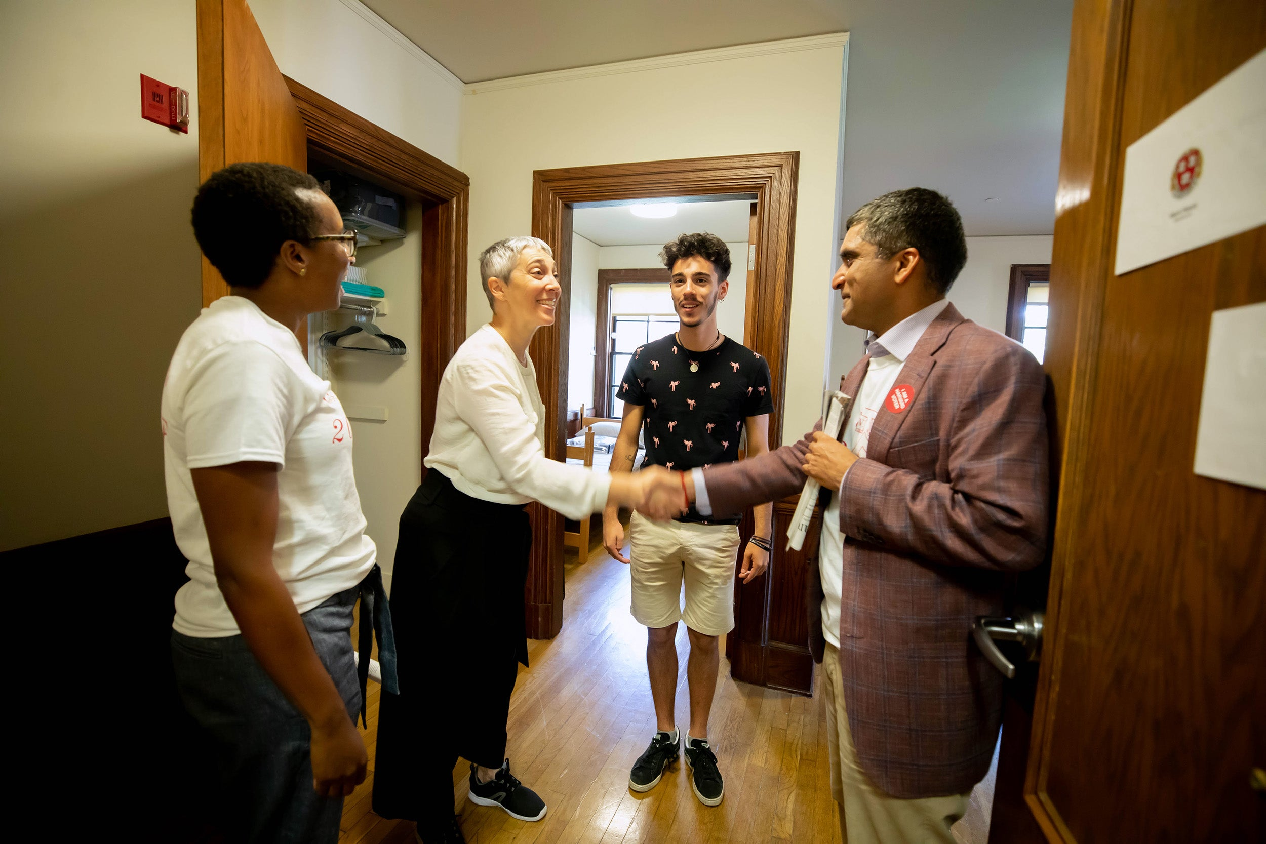 Deans greet a parent and student