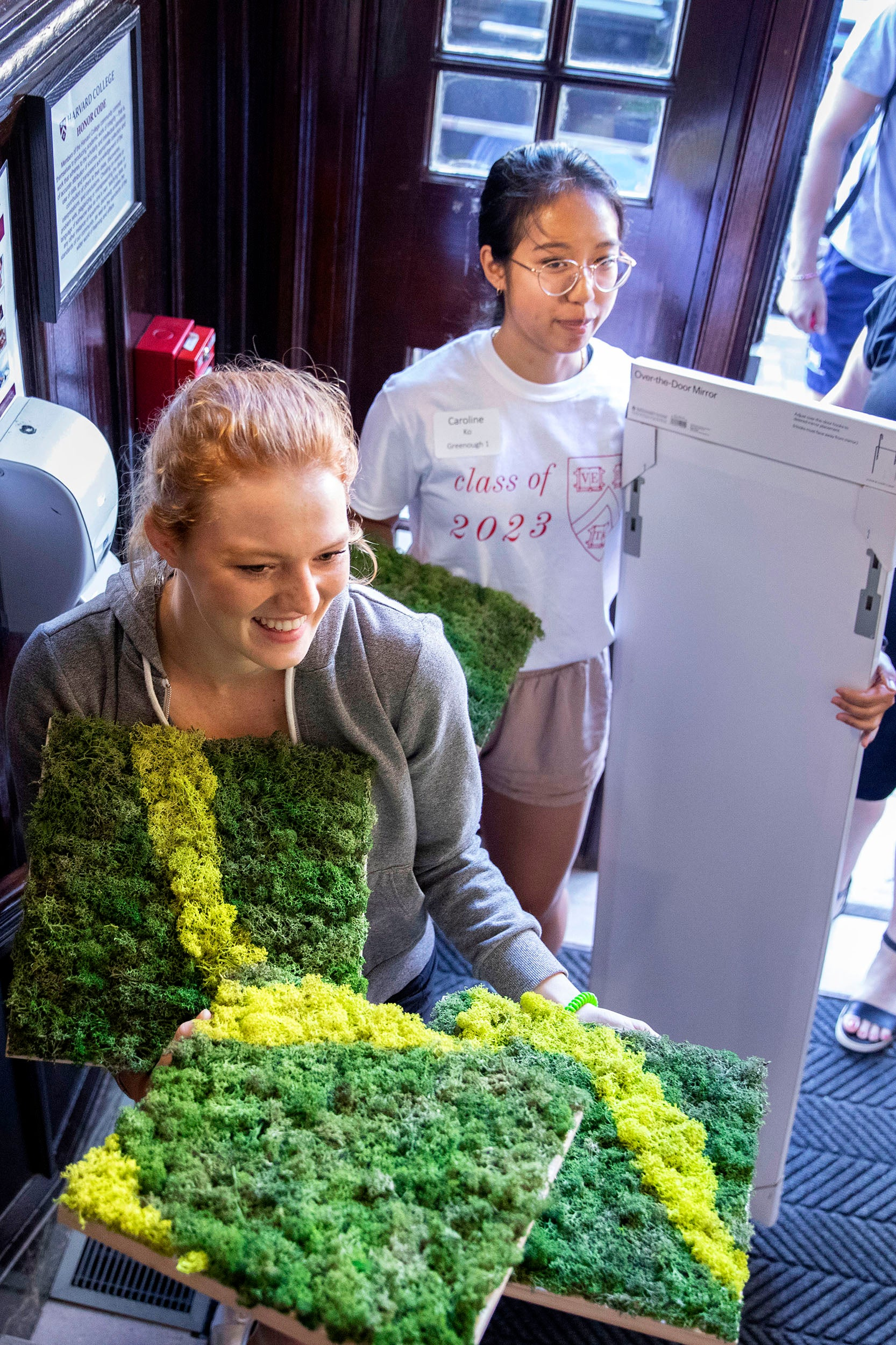 Students carrying panels of green moss