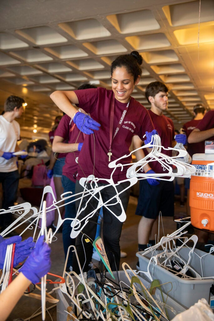 Student untangling coat hangers