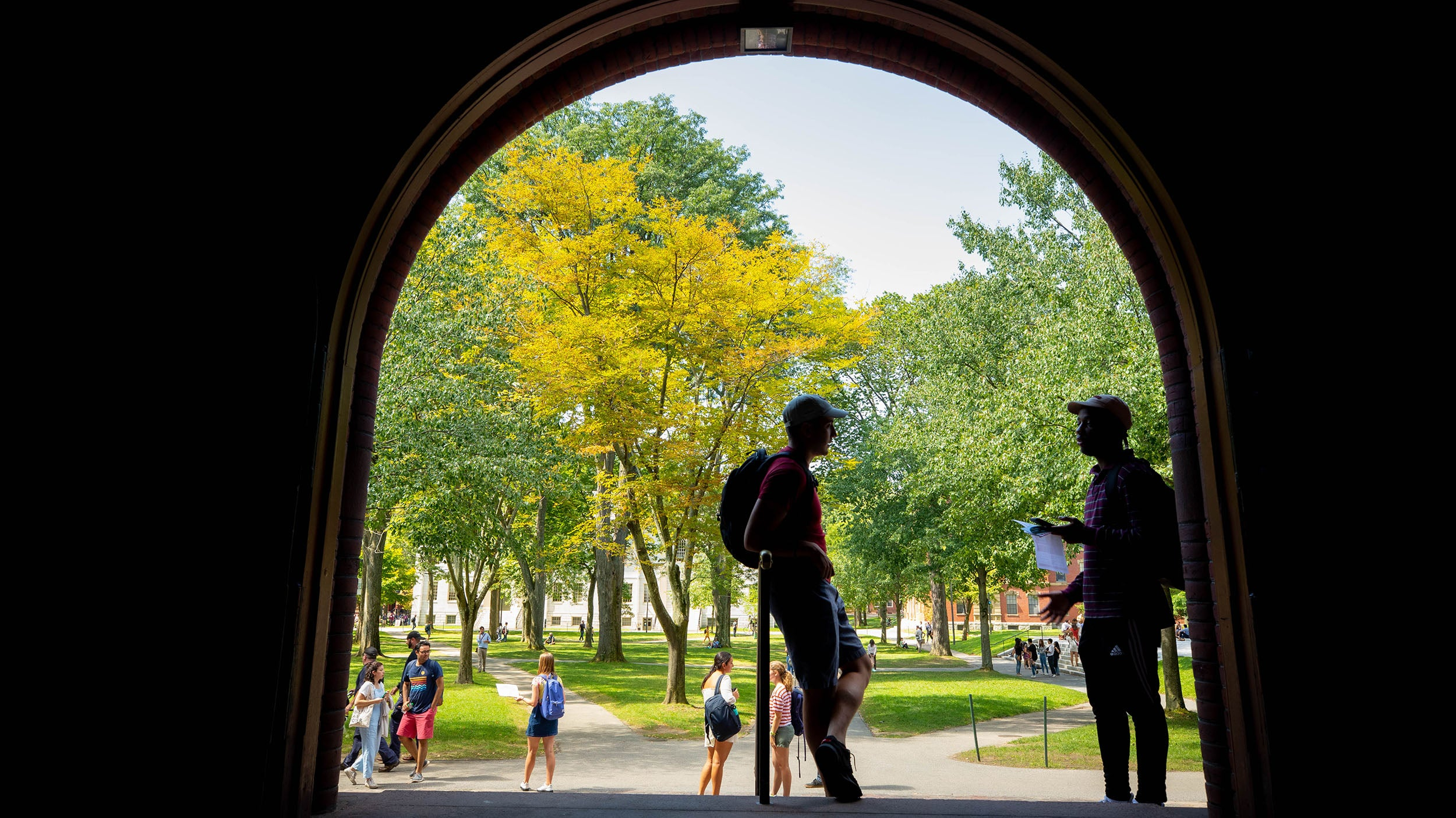 Two students stand under Sever Hall archway.