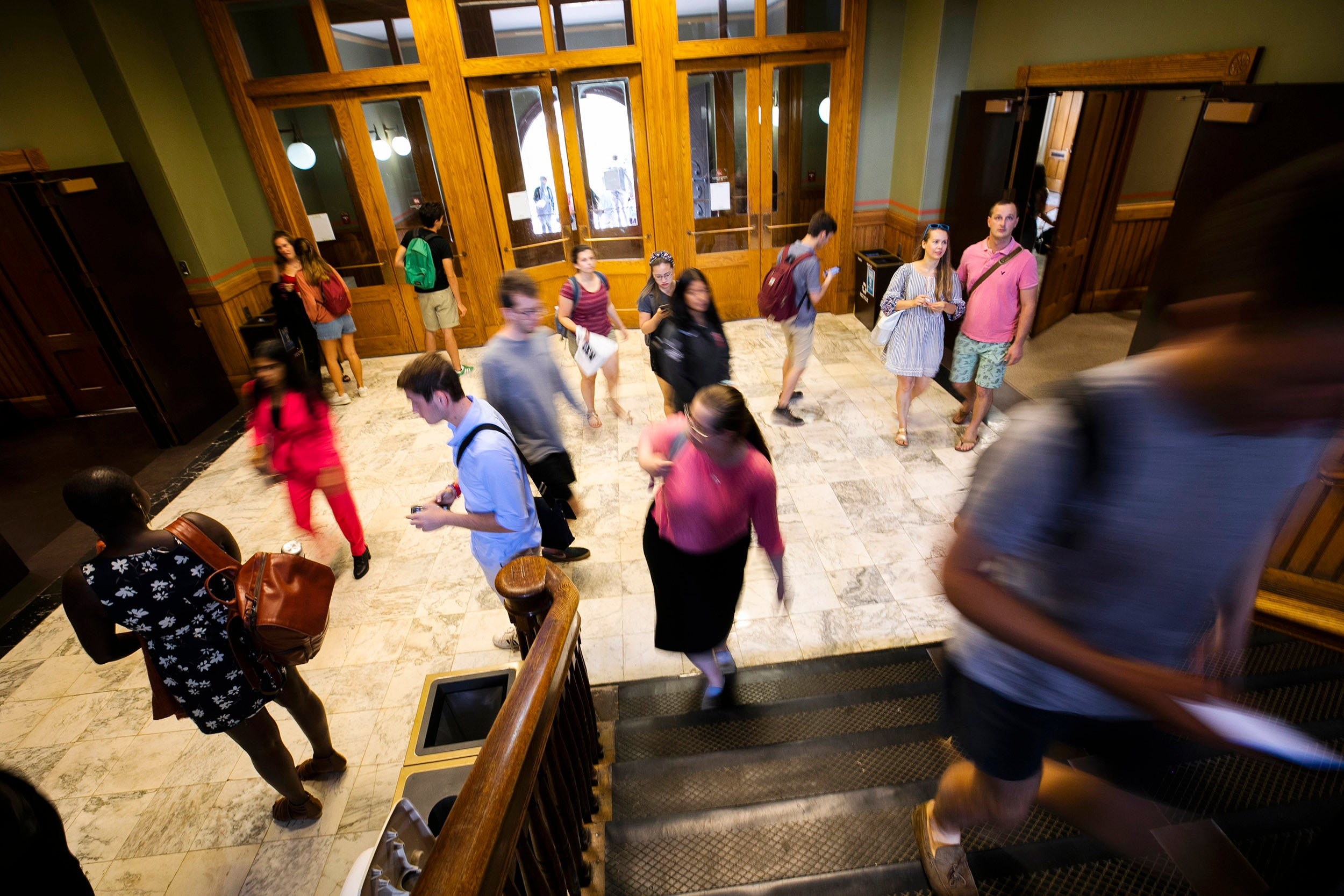 Students walk around the entrance to Sever Hall.