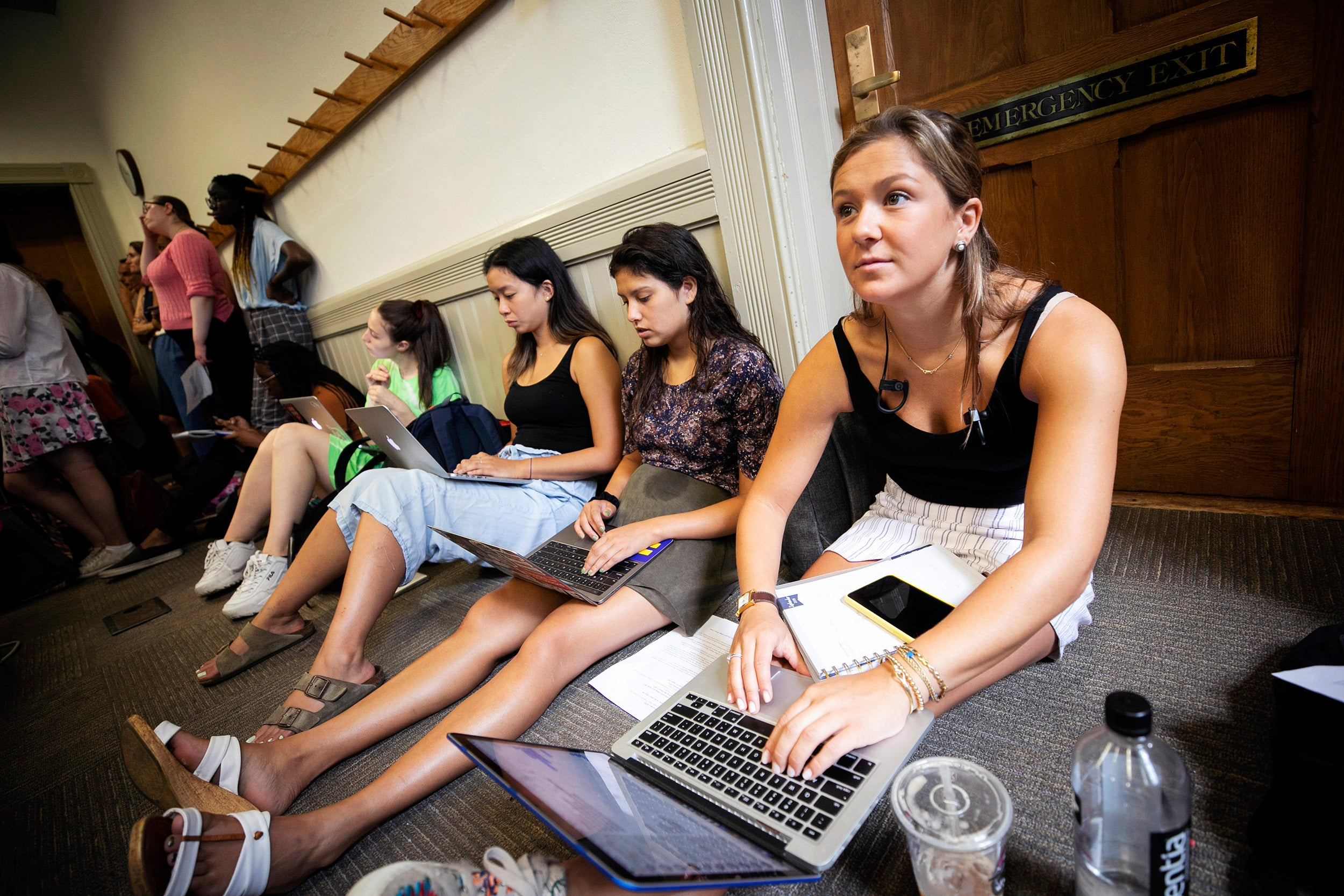 Students sit on floor listening to lecture.