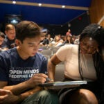 two students looking at notebook together