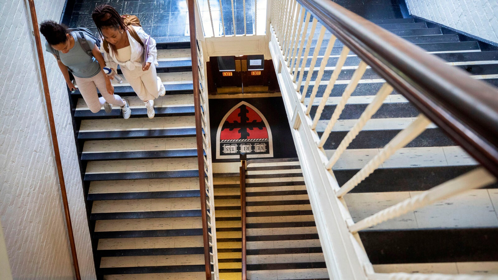 Two students walk down stairs in Pierce Hall.
