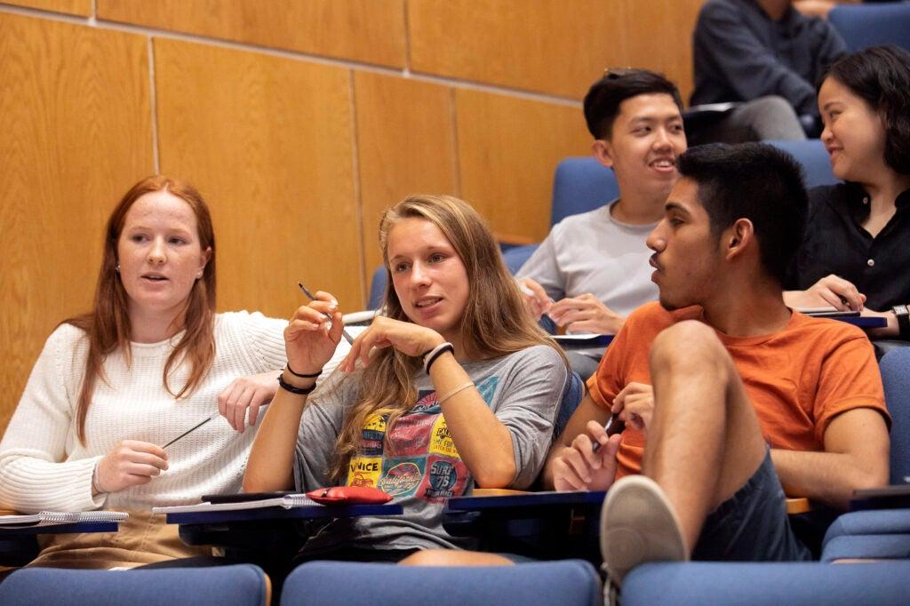 Three students speak during class.