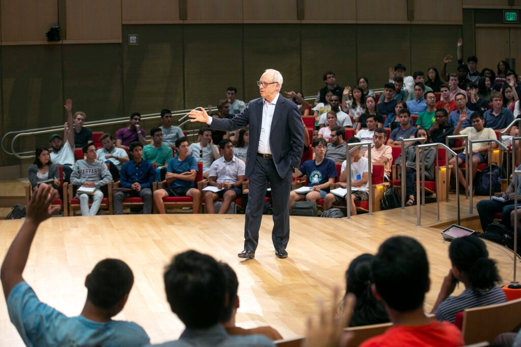 Michael Sandel speaks from the stage during class.