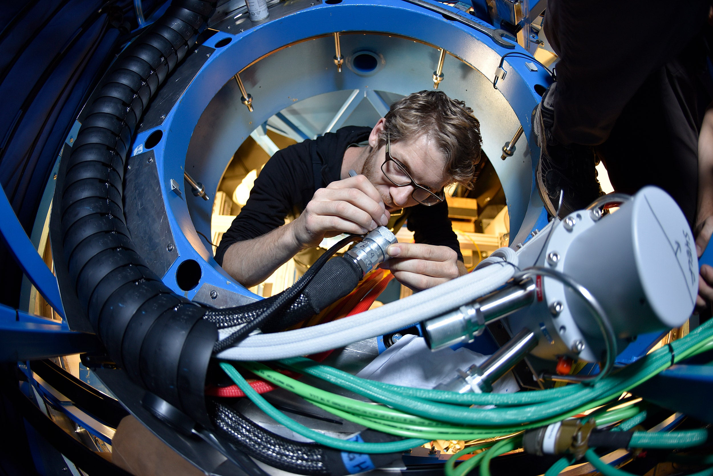 Jamie Tolan cleans cryogenic hoses for the BICEP3 telescope.