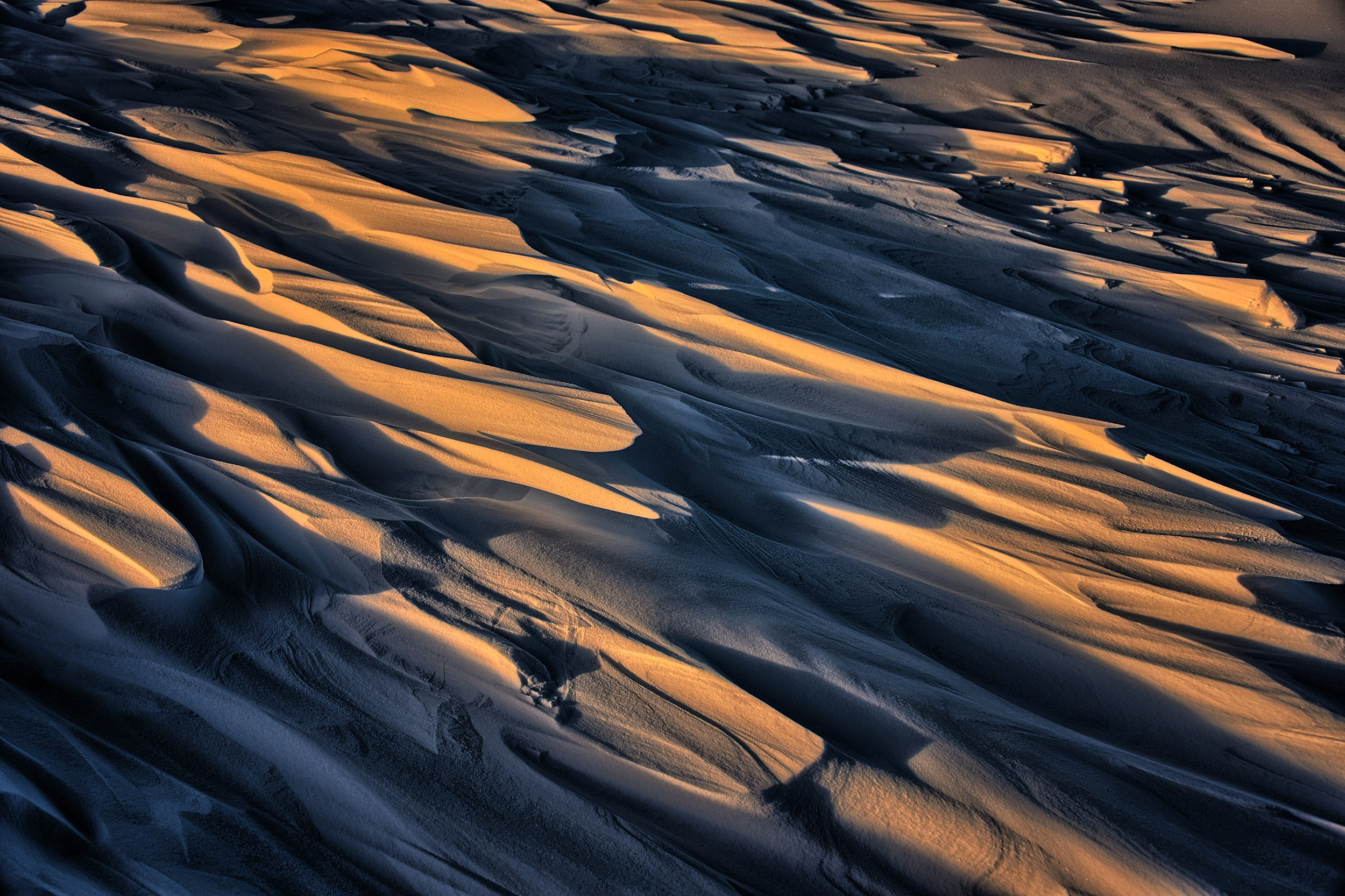 Dune-like formations sculpted by the wind called Sastrugi cast shadows on ice.