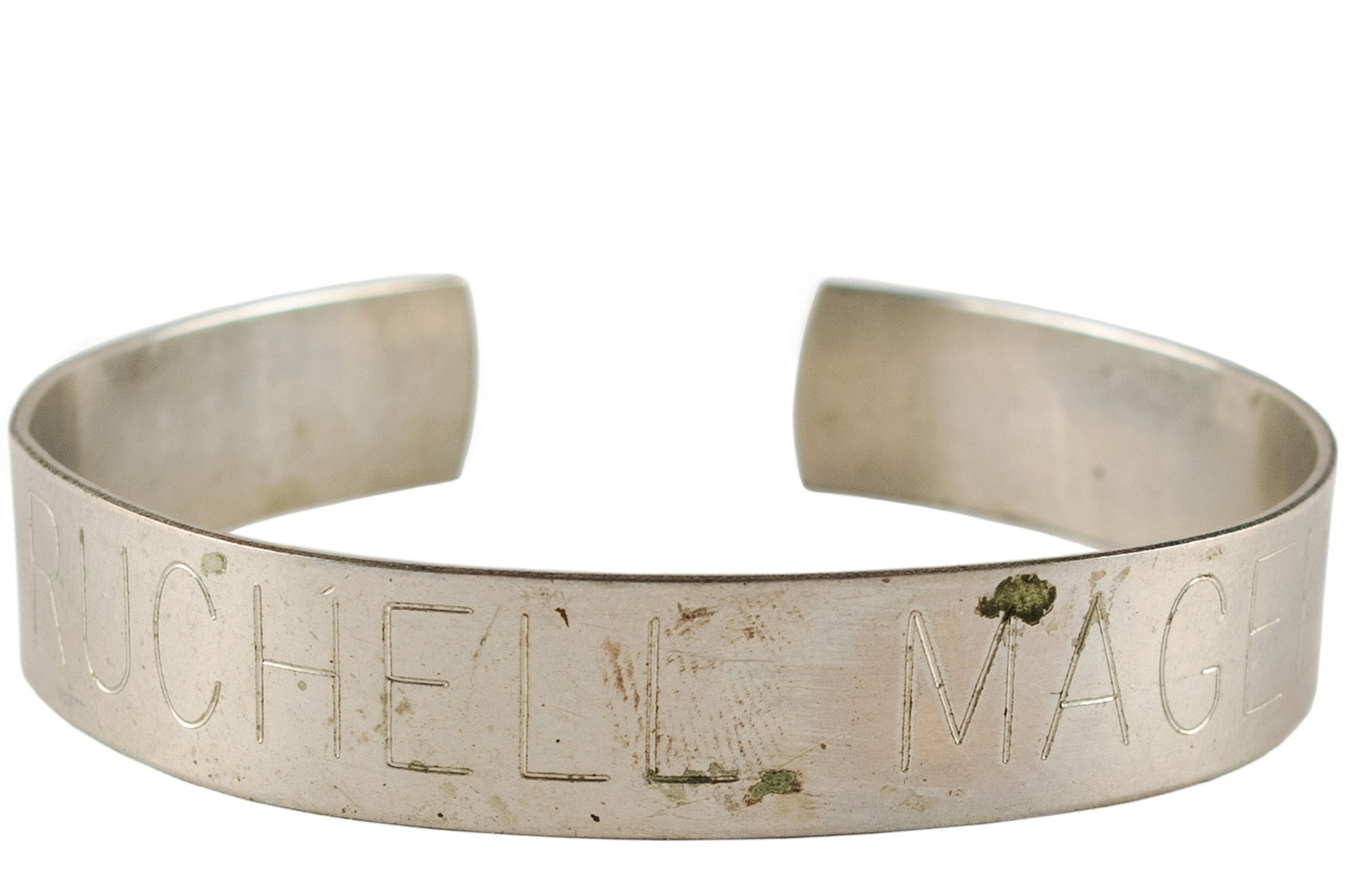A metal bracelet engraved with the name Ruchell Magee.