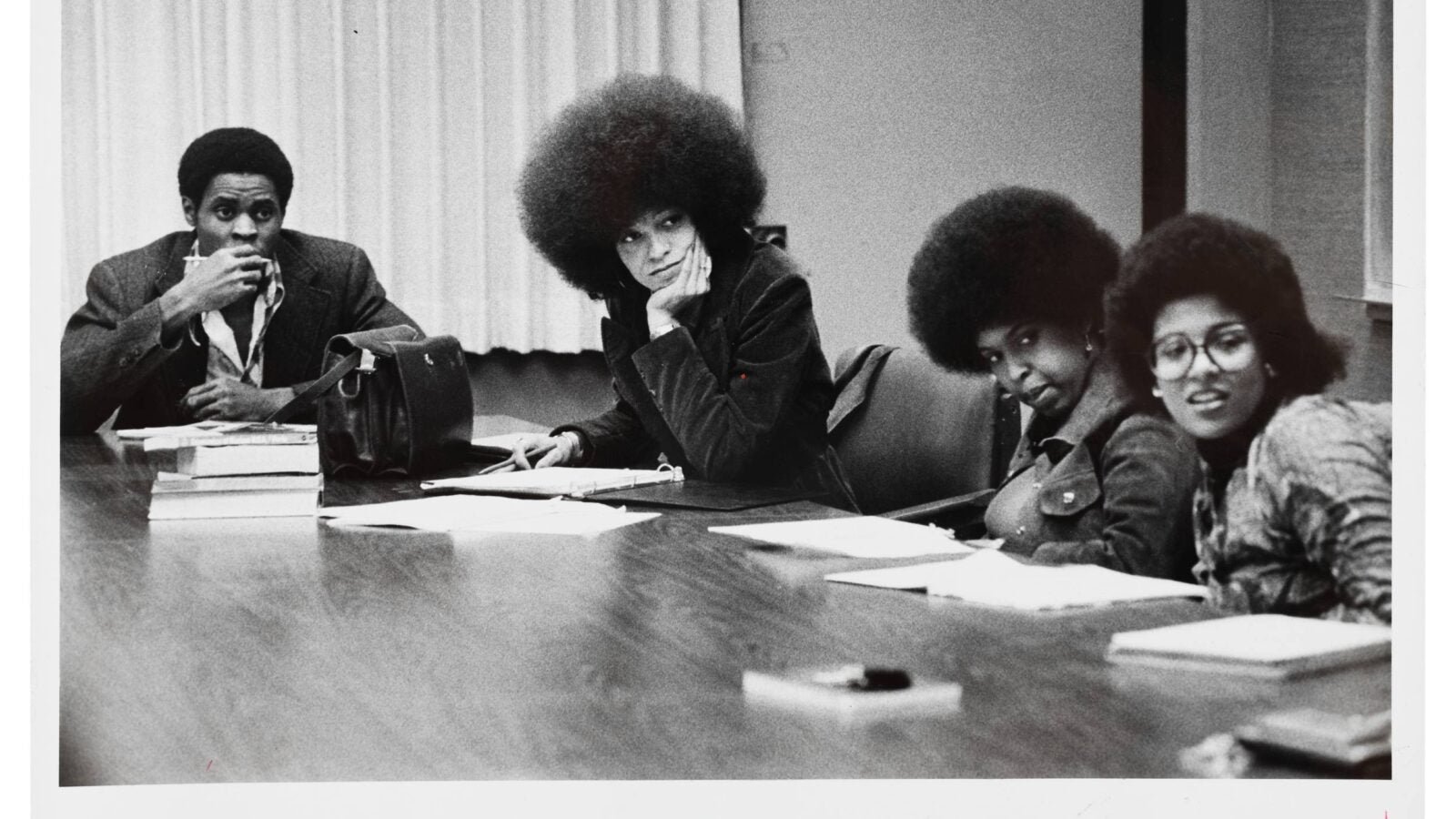 A black and white photo of young Angela Davis sitting at a conference table with three other people